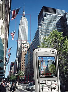 Boxes appear on the phone's screen, highlighting known businesses and landmarks, such as the Empire State Building. The user can click one of these boxes to download information about that location from the Web. In Nokia's mobile-augmented-reality prototype, a user can point a phone's camera at a nearby building; the system calculates the building's location and uses that information to identify it.
