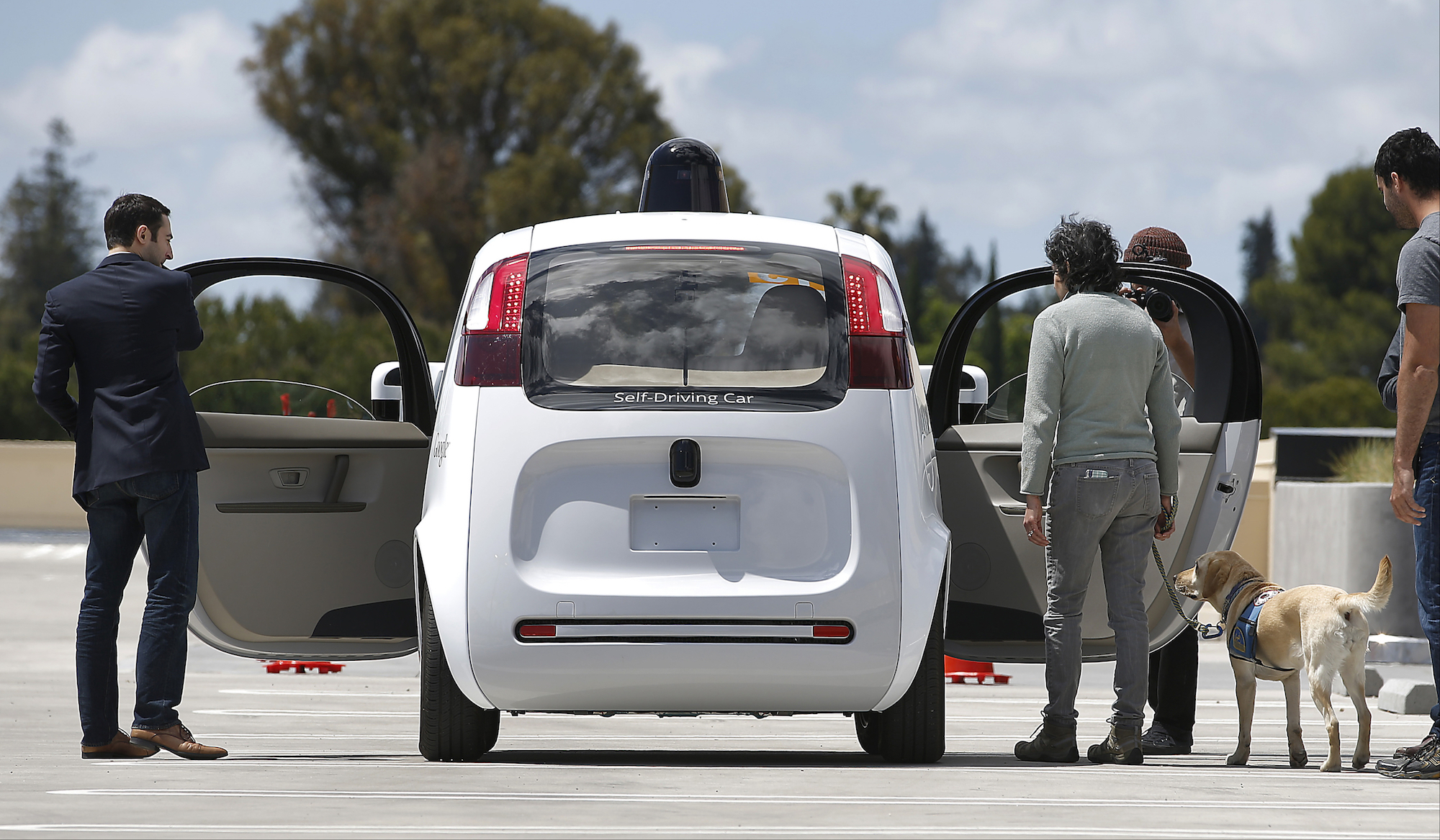 Passengers get into a self-driving car.