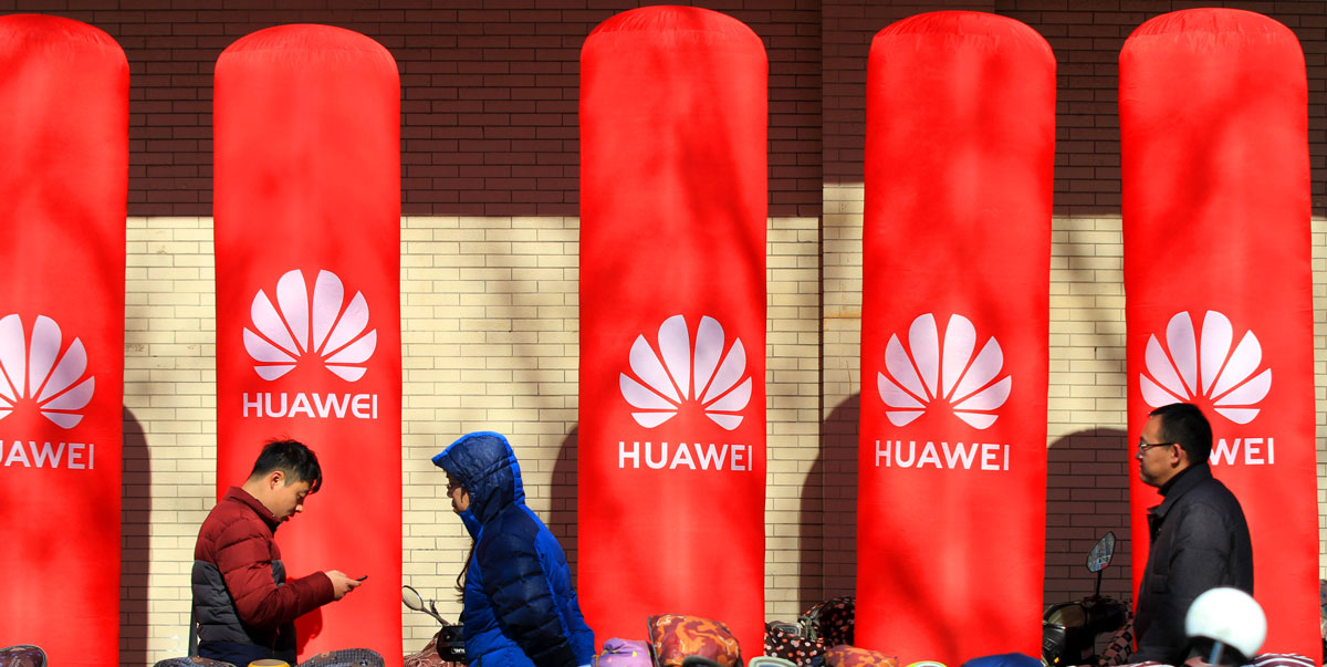 Pedestrians walk past an advertisement for Huawei