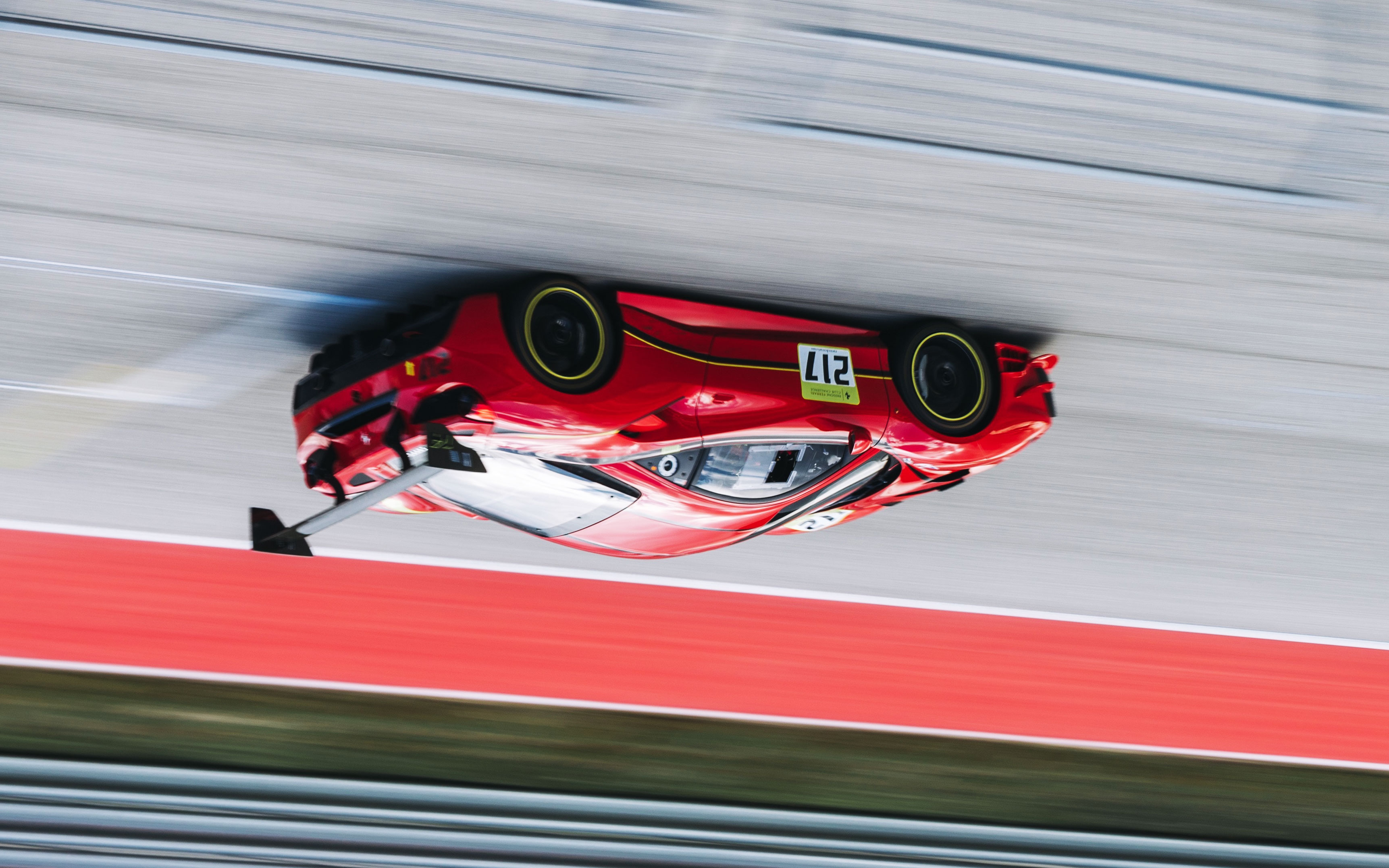 An image of a race-car on a track, rotated to appear upside-down.