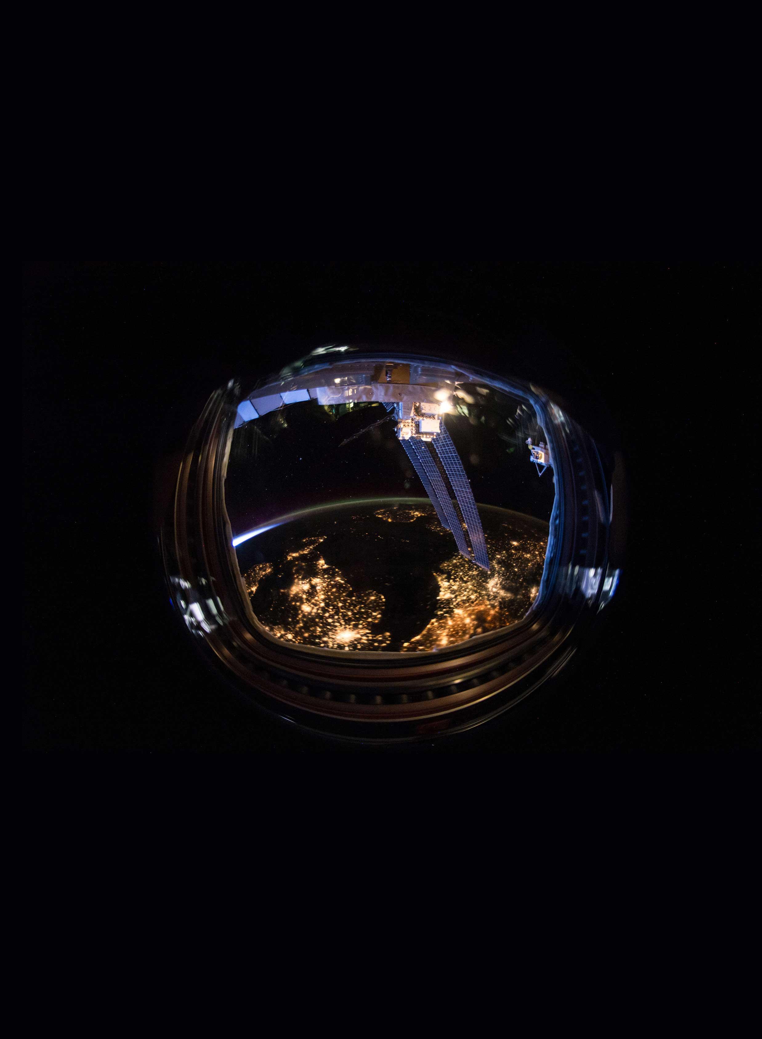 An astronaut helmet reflecting a light-filled earth