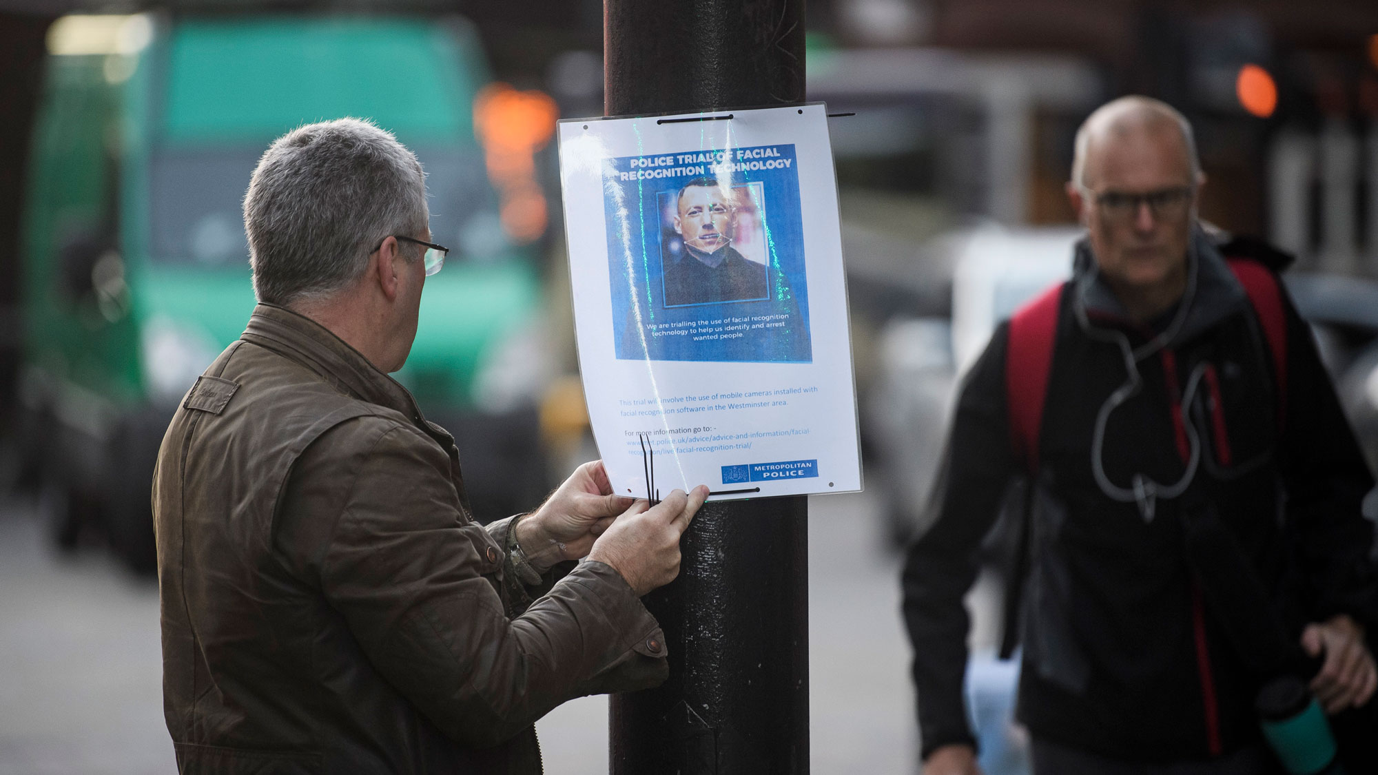 A man puts up a poster describing London's Metropolitan Police's face recognition system trial
