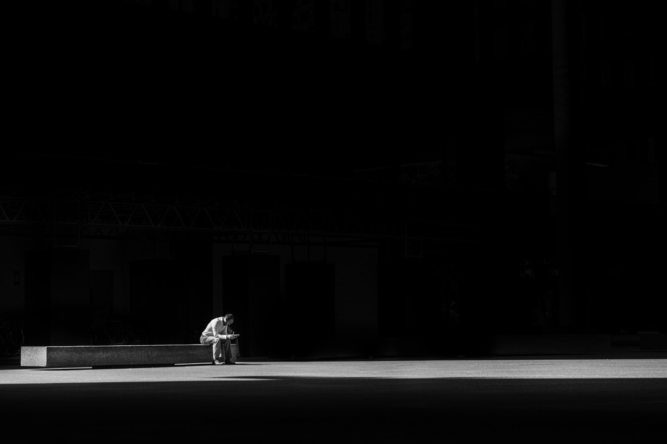 image of man sitting alone at bench looking at phone