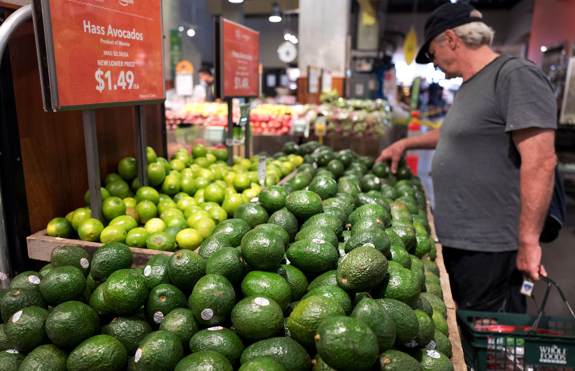 A man shops for avocados in Whole Foods in New York