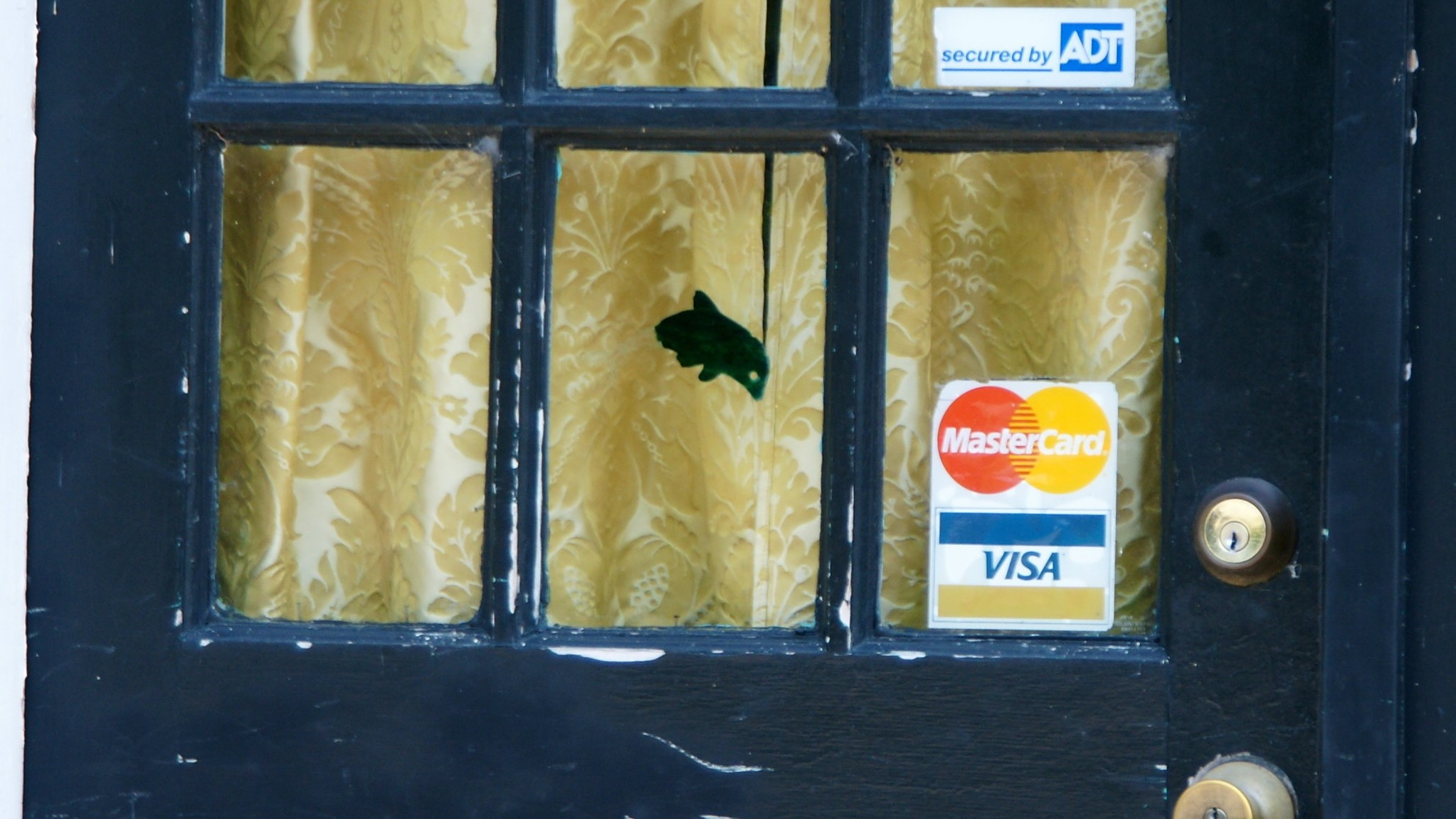 A merchant's closed door, displaying the Visa and Mastercard logos.
