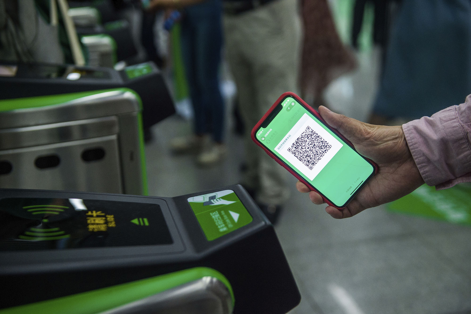 A transit rider uses their phone to pay a fare using WeChat pay.