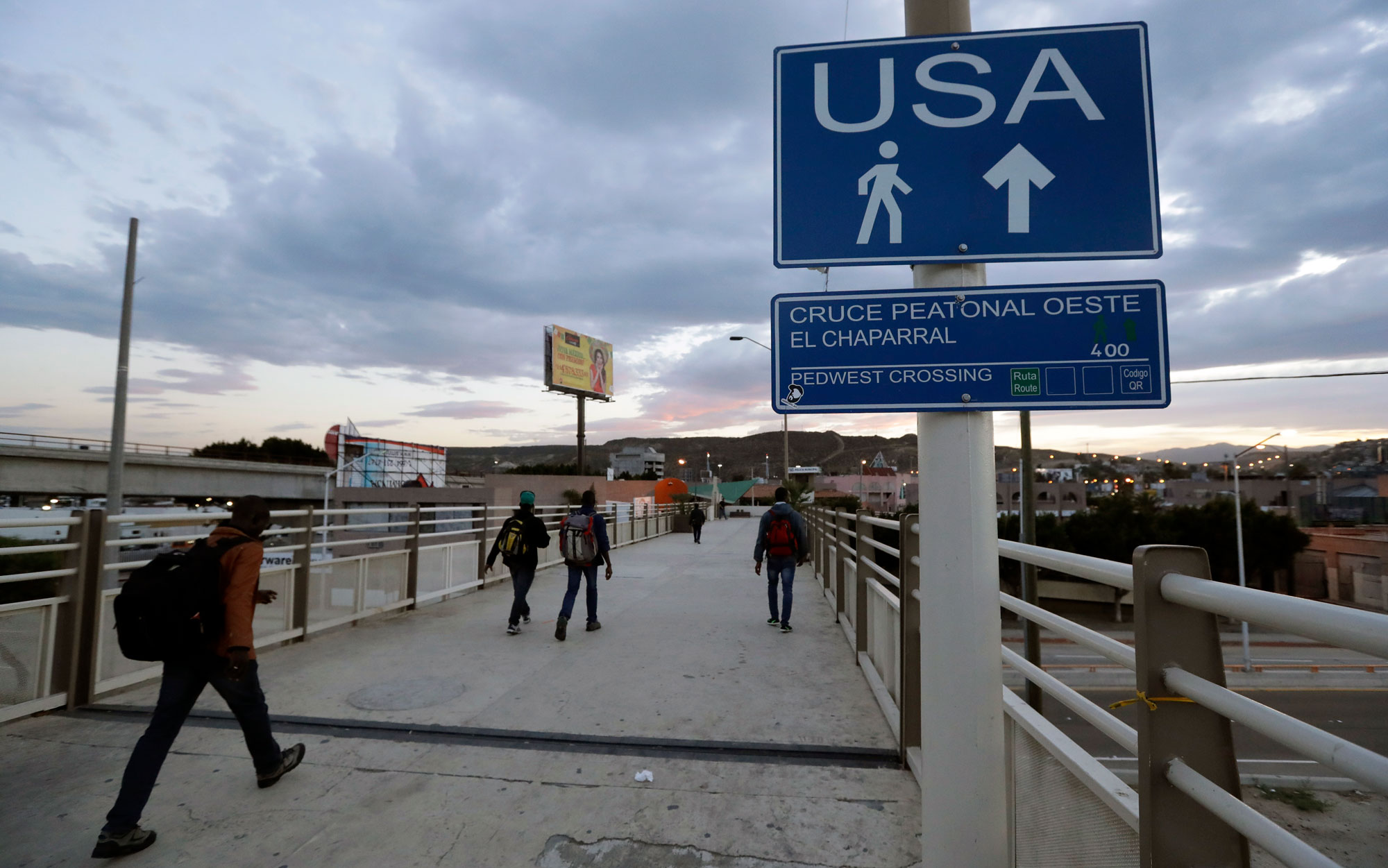 People walk towards the US border crossing in Mexico