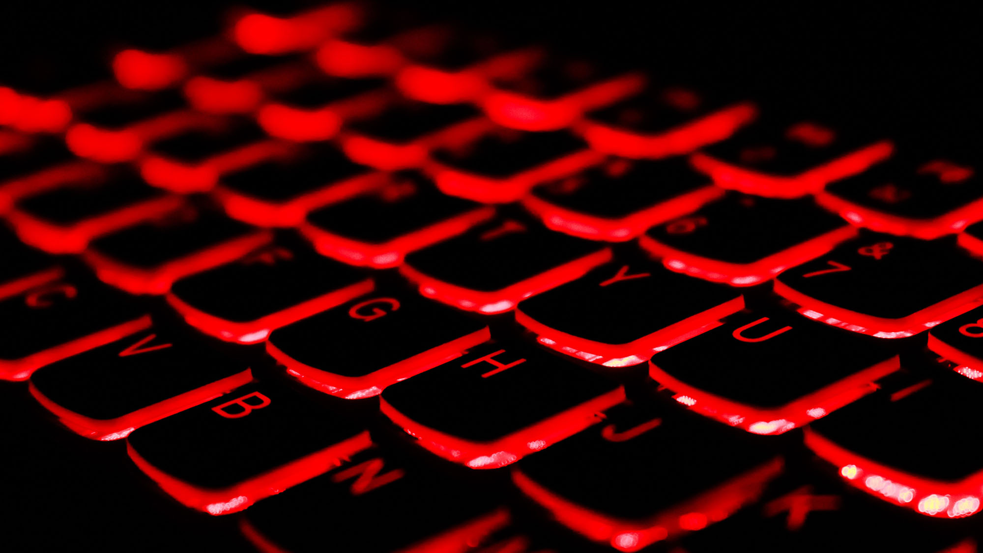 An image of a computer keyboard in the dark, with a red back light.