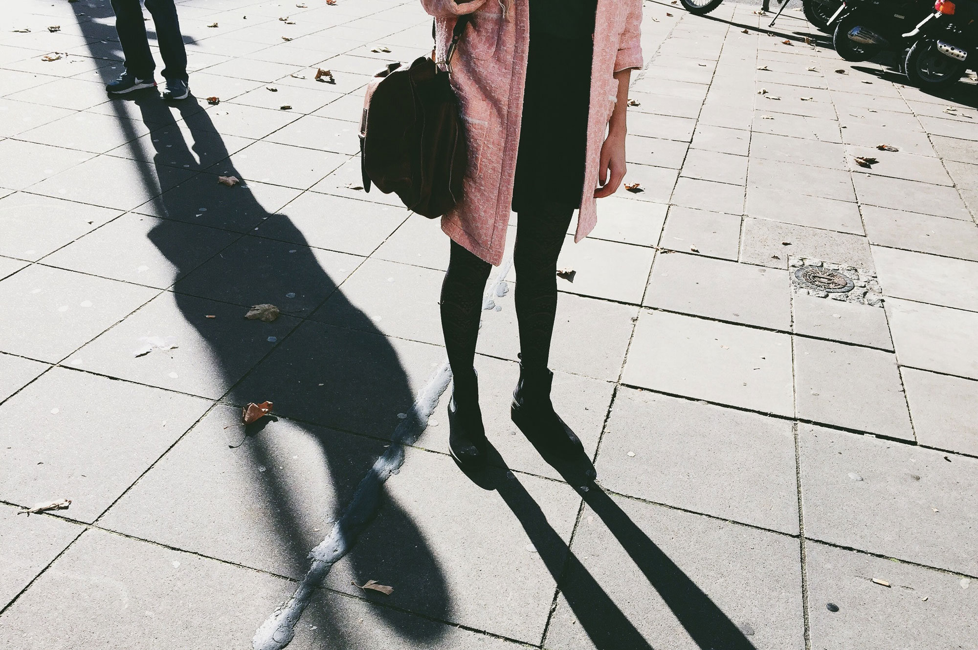 A man's shadow behind a woman who is on her phone