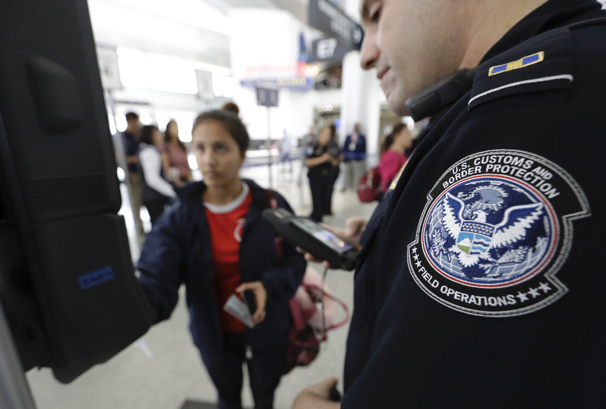A U.S. Customs and Border Protection officer helps a passenger navigate a facial recognition kiosk at the airport.