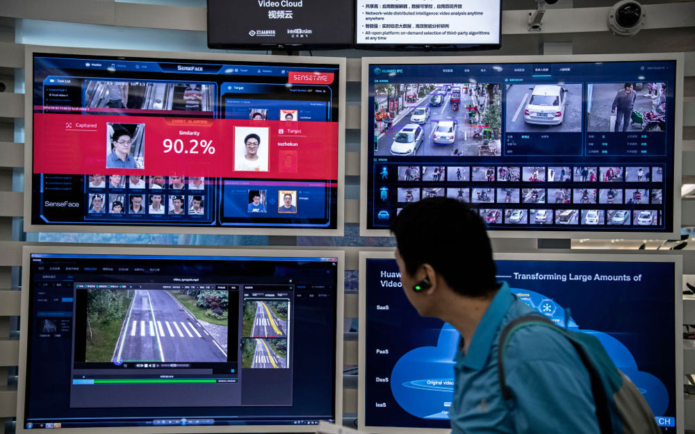 A man walks in front of screens showing facial recognition systems in action