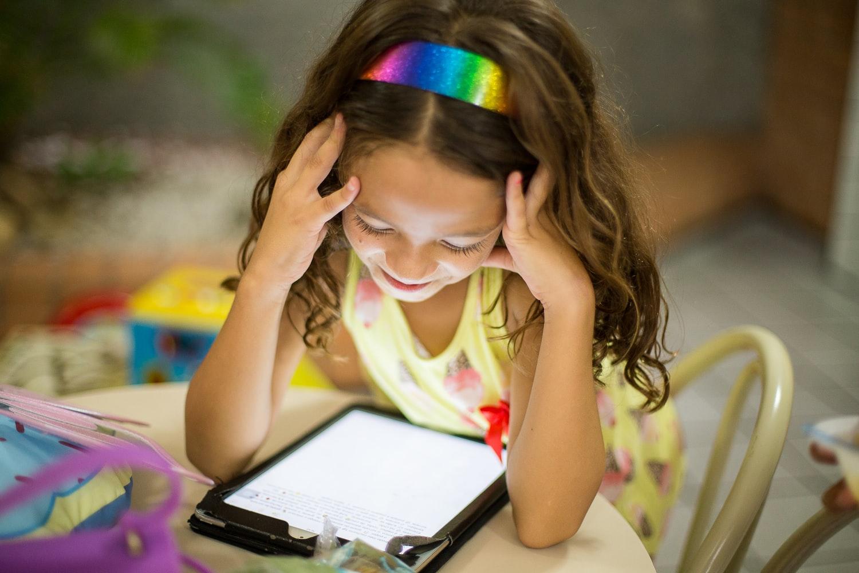 girl with rainbow headband reading tablet kindle