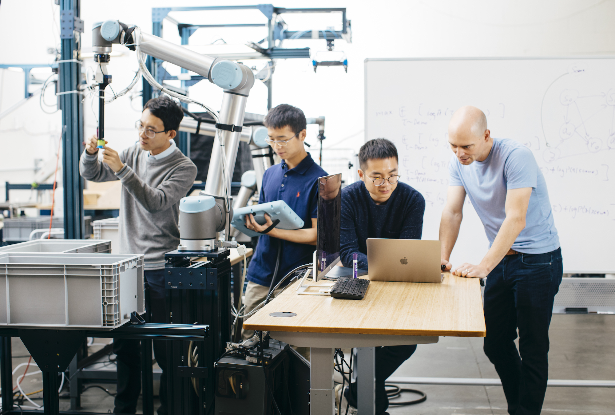 Covariant co-founders work on their robotic arm.