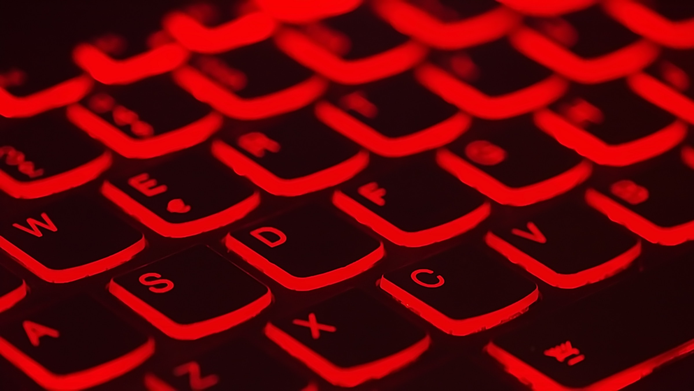 A black keyboard with a red backlight.