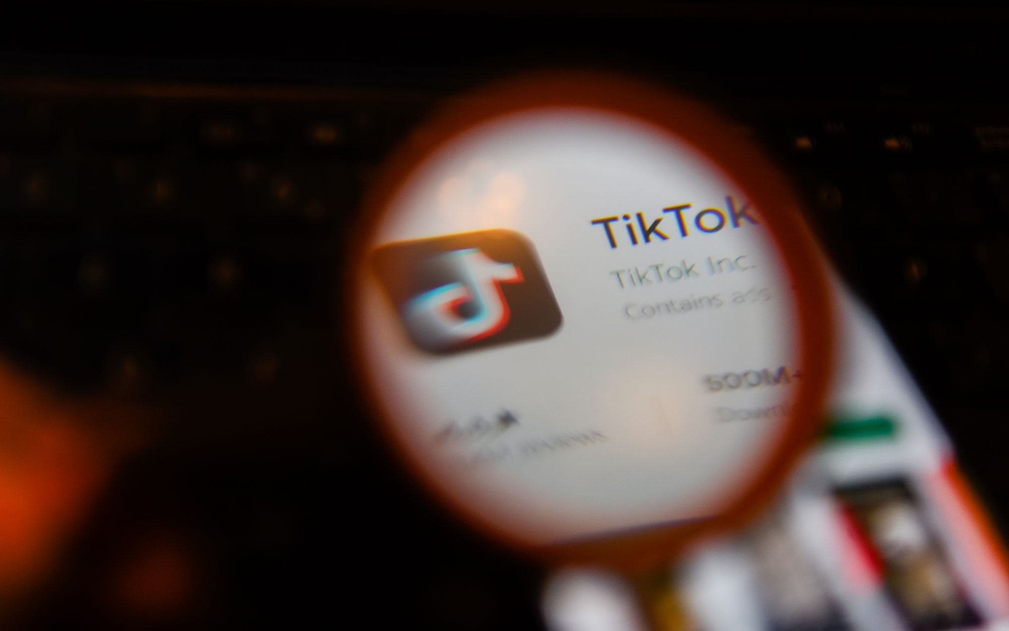 TikTok's app on a smartphone, with a magnifying glass in front