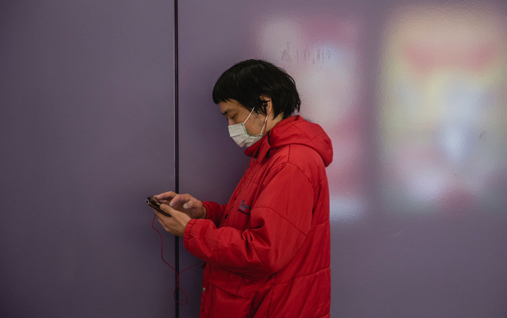 A man in Hong Kong in a face mask checks his phone