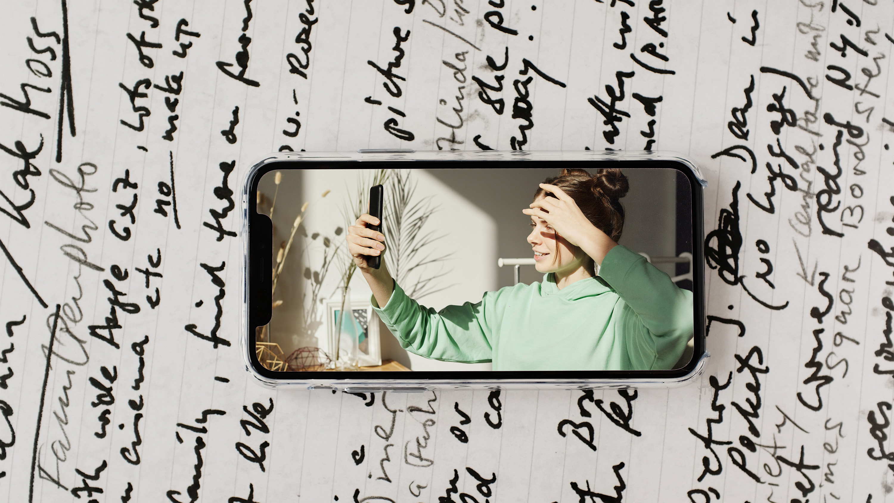 image of woman in green sweatshirt hoodie taking selfie with phone in apartment during coronavirus quarantine on phone with journal background isolation journal suleika jaouad