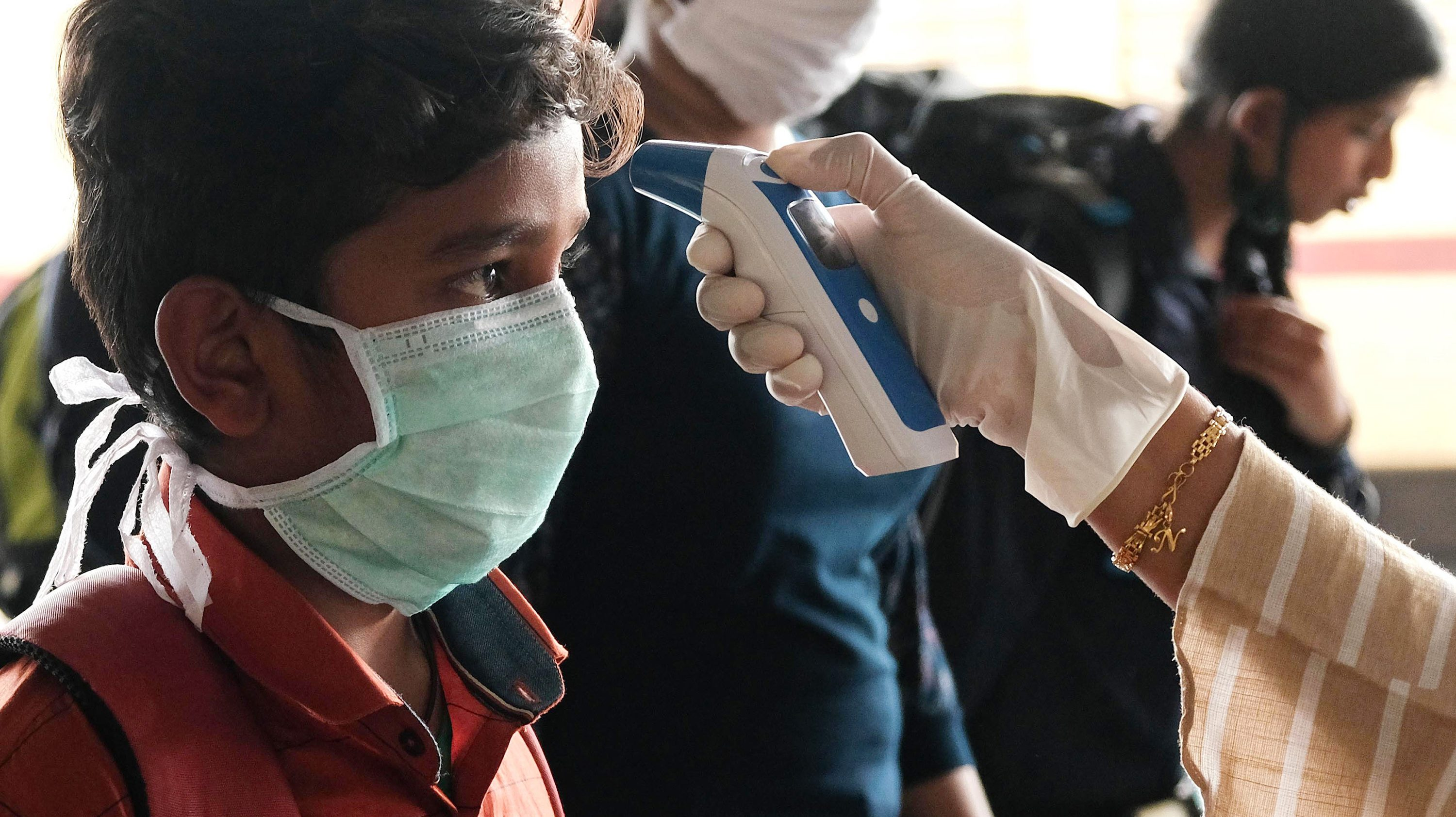 A government health worker in Kerala checks a boy's temperature.