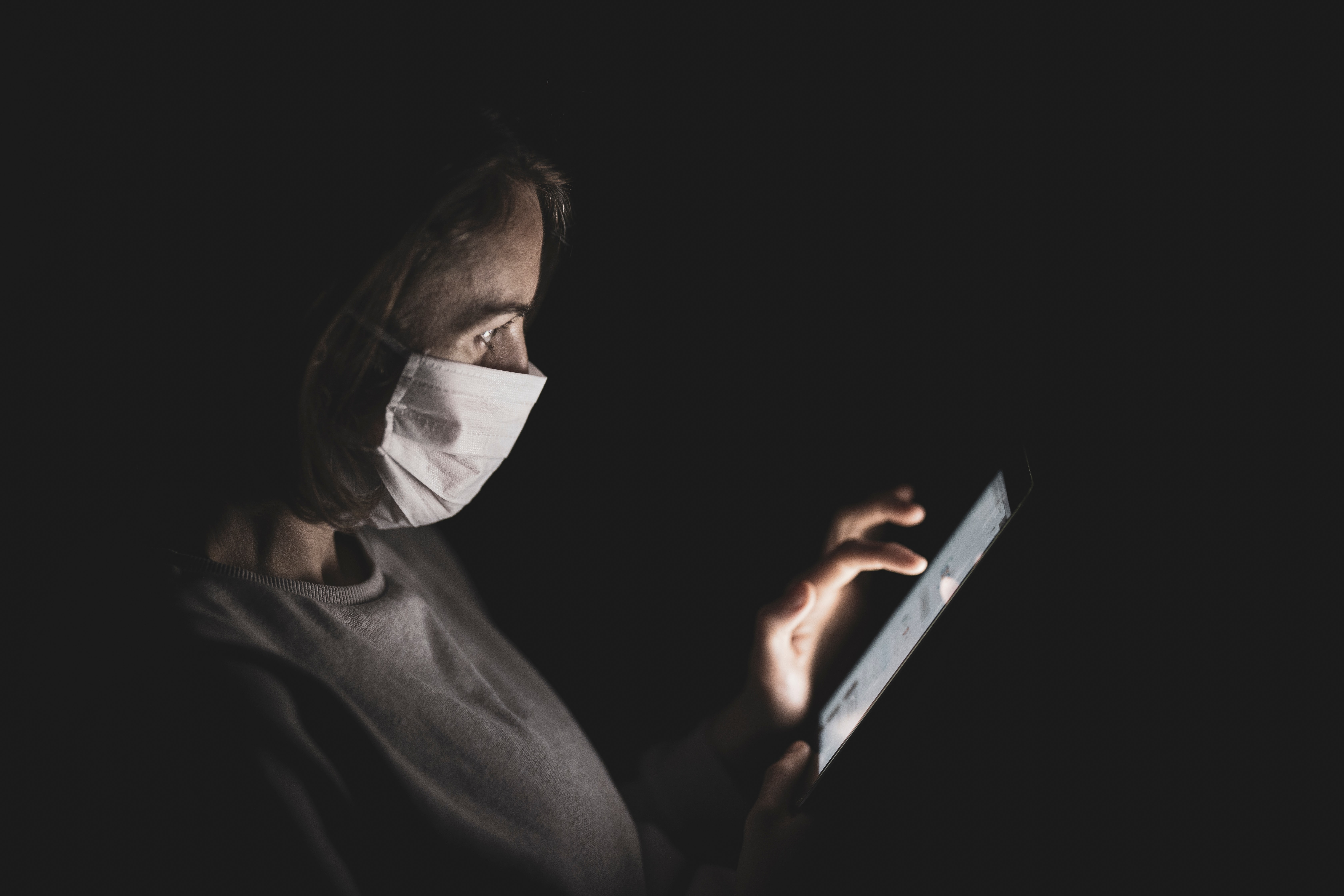 masked person looking at screen