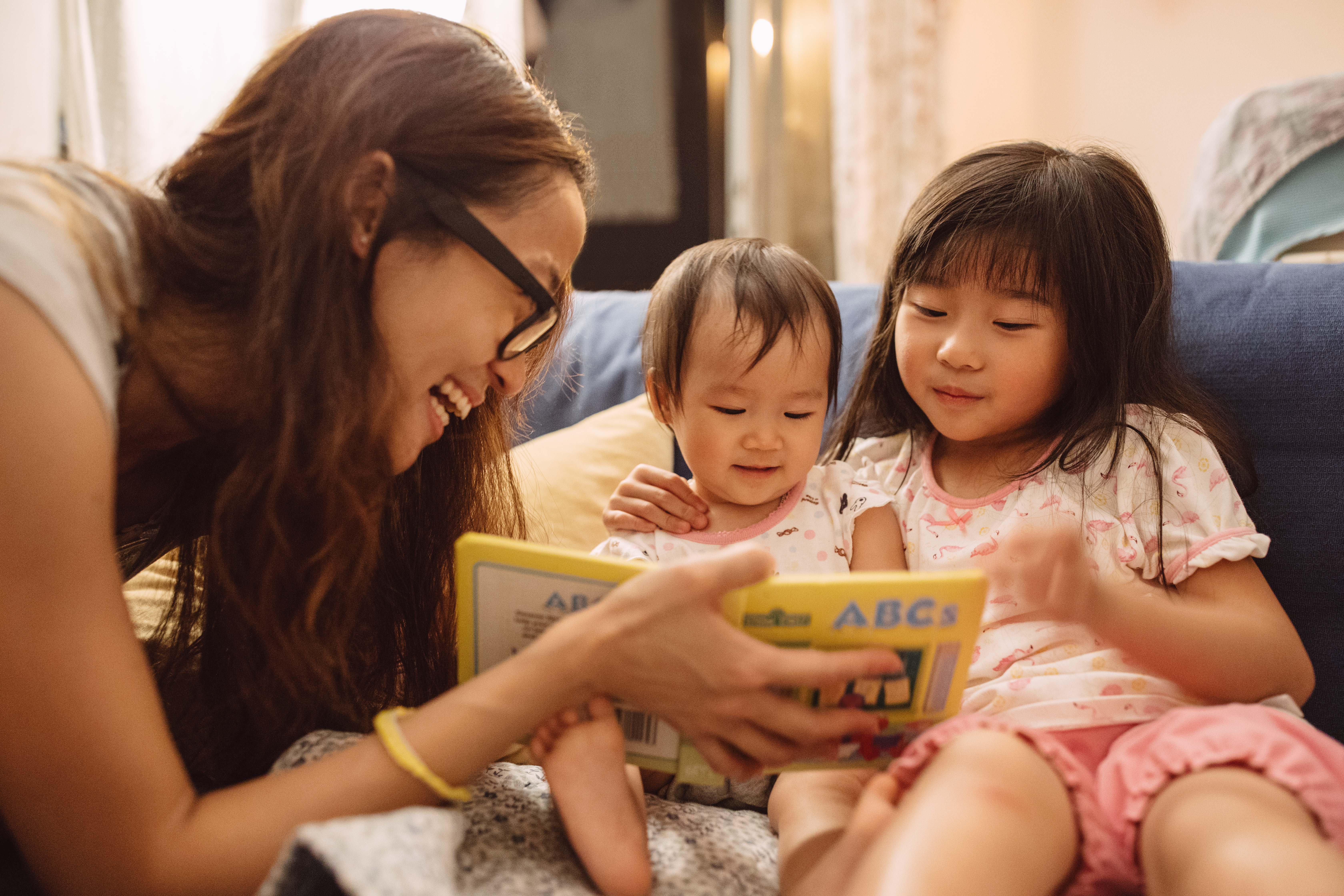 Mom reading story book to her daughter and baby on the couch.