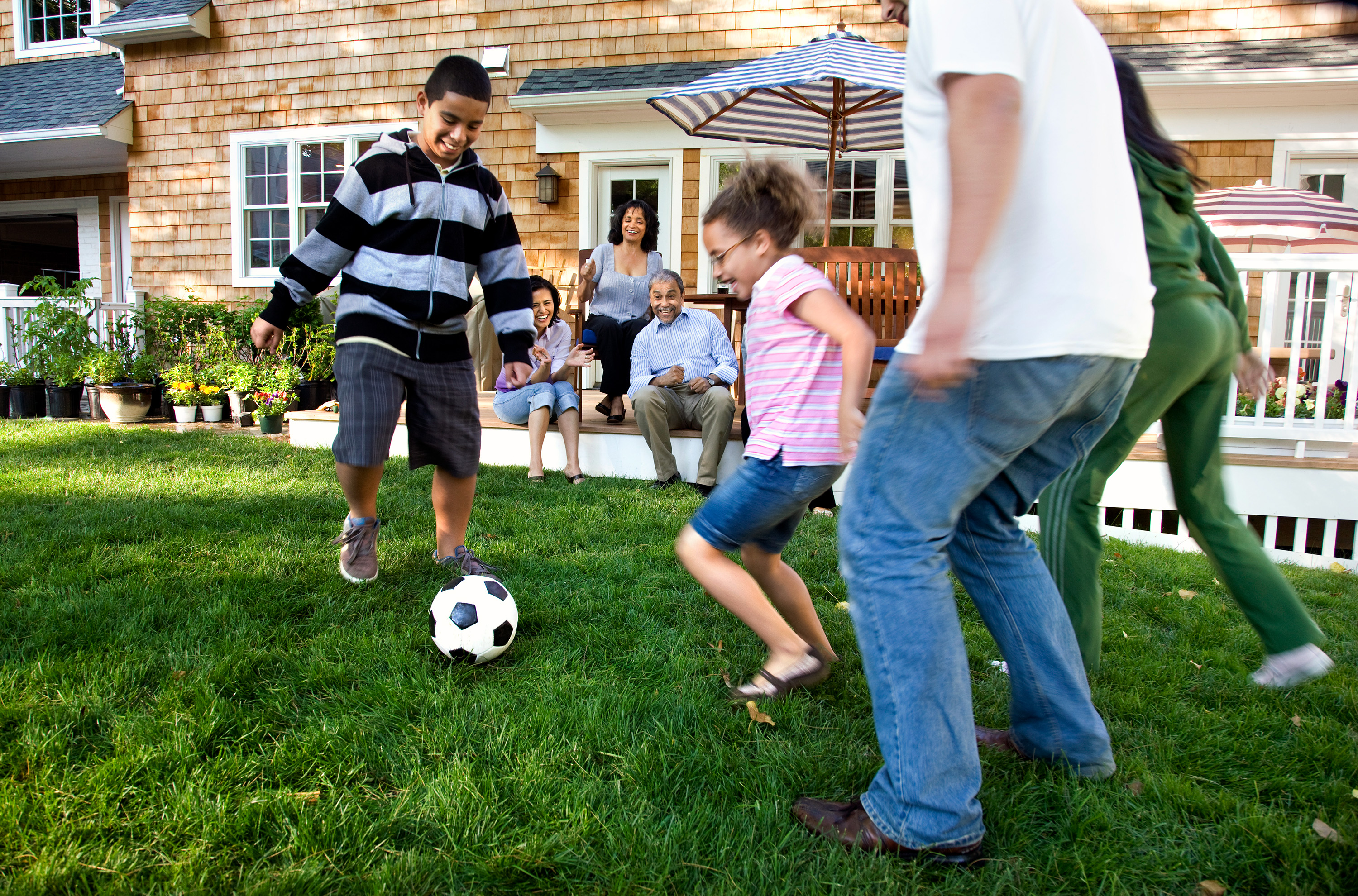 Photo of a family playing soccer in suburban backyard