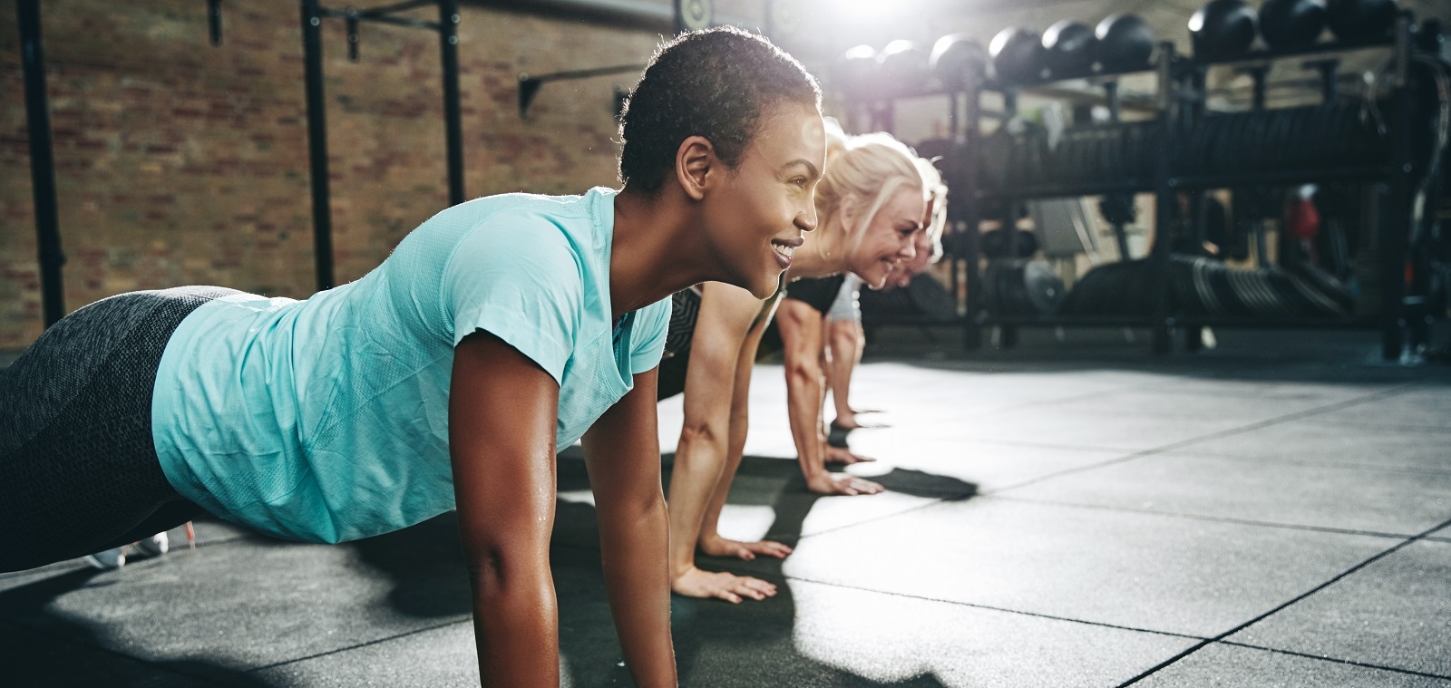 Smiling young African American woman in sportswear doing pushups at the gym with a group of friends during an exercise class; Shutterstock ID 1336697780; Project Title: FY20 Q1 Phase 3 Perspectives Images; Job: CR21702_Q2_Perspectives_Images; Client Cross-Charge: 1001-2040-682677; Team + Client Name: Rachael Henke-Brand Campaigns