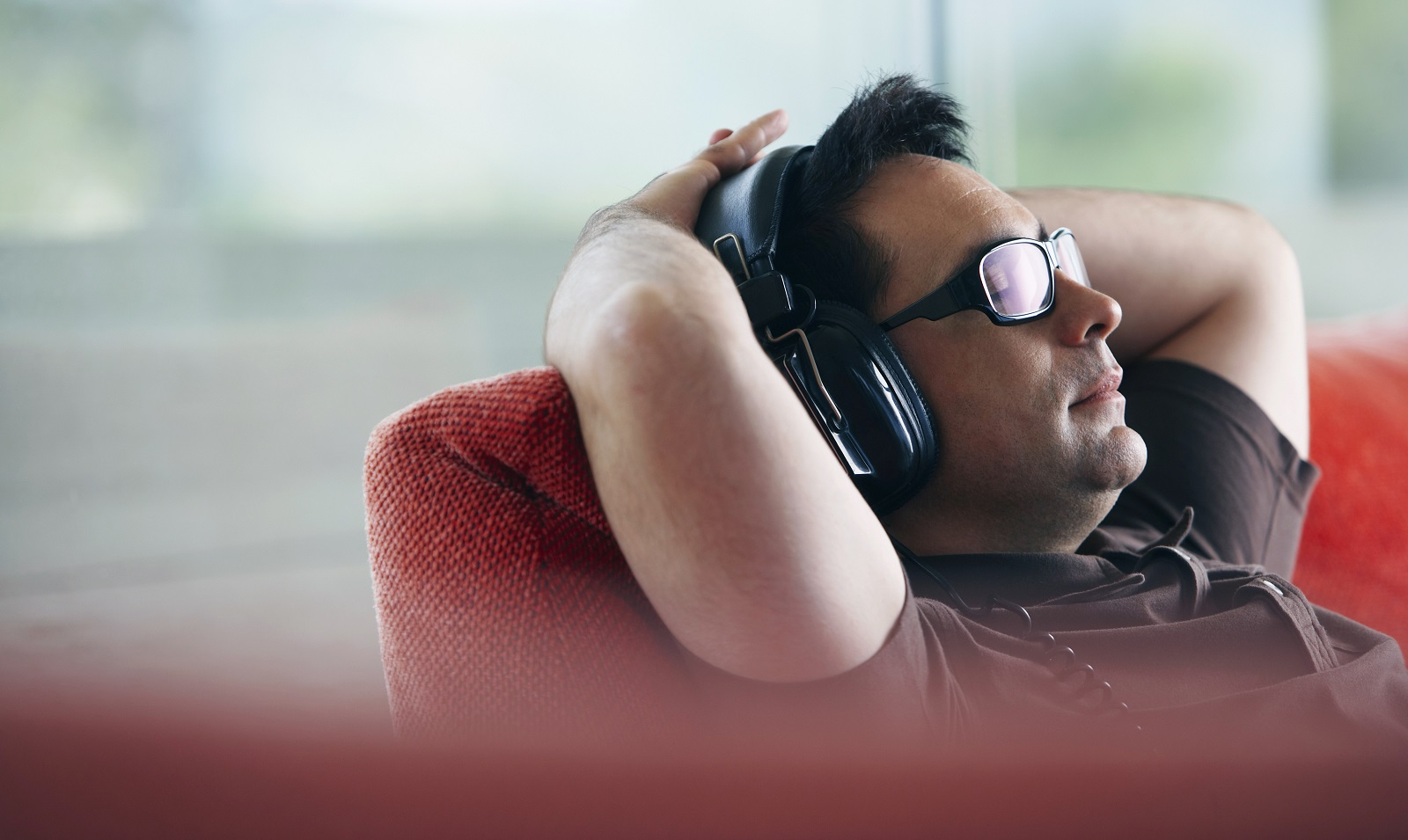 Man relaxing at home listening to headphones on couch.