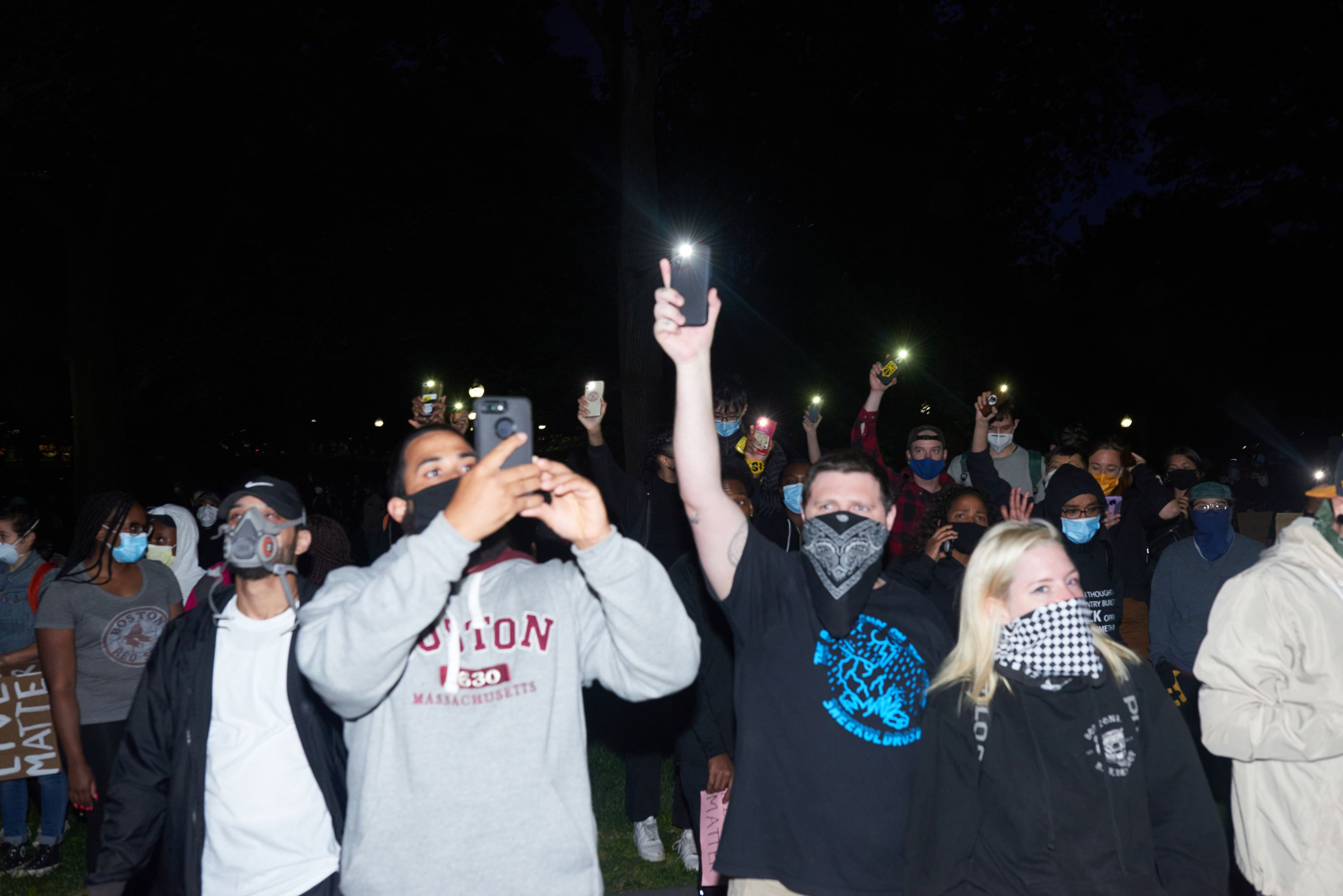 Photograph of a crowd at a BLM protest with smartphones recording