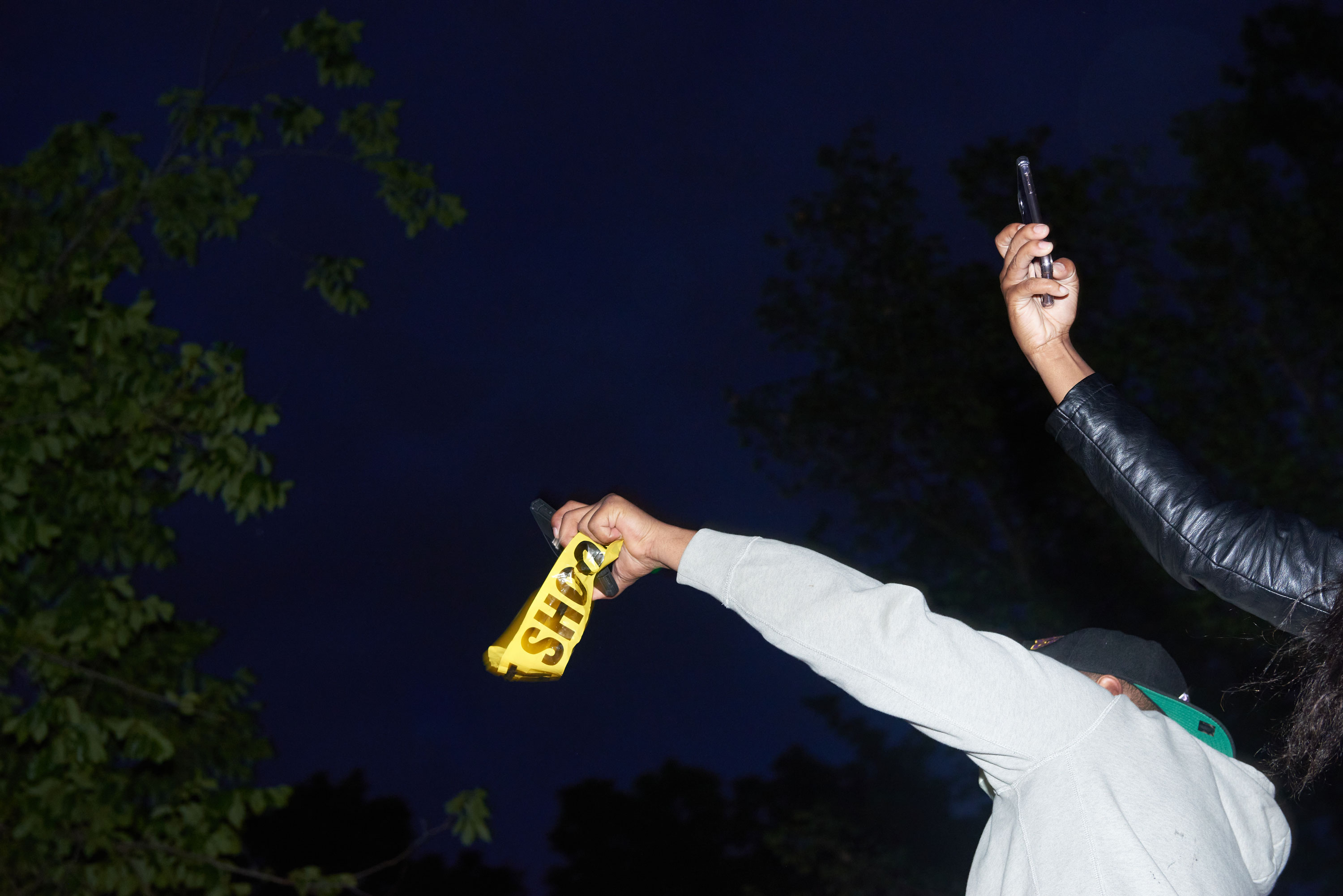 photograph of two protestor arms holding up smartphones in the night
