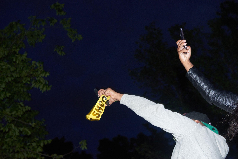 عکس دو دست معترض که شب ها تلفن های هوشمند را در دست دارند