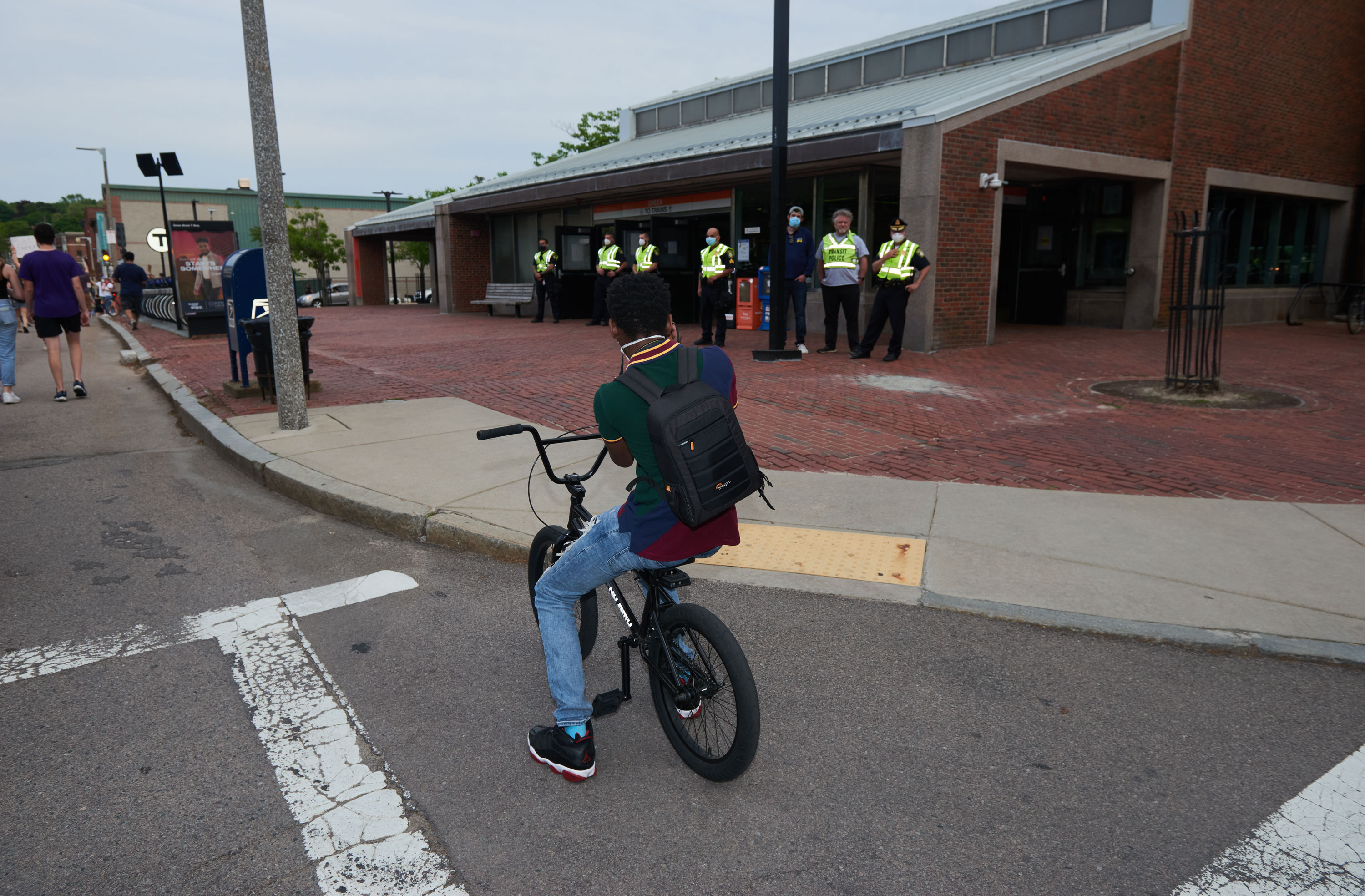 photograph of a young boy on a BMX bike photographing the police outside an MBTA station in Boston