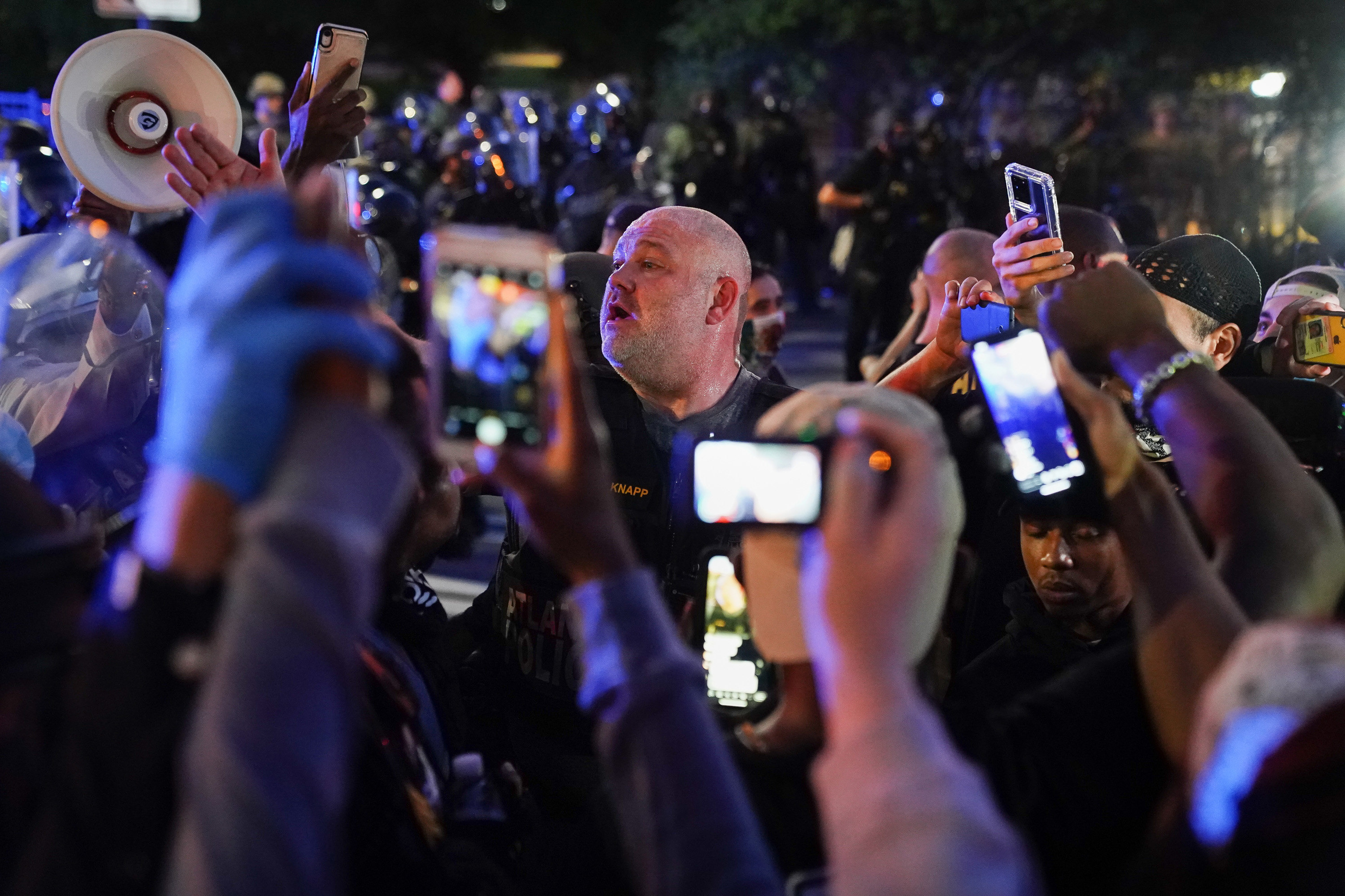 People in a crowd filming at night with cellphone cameras