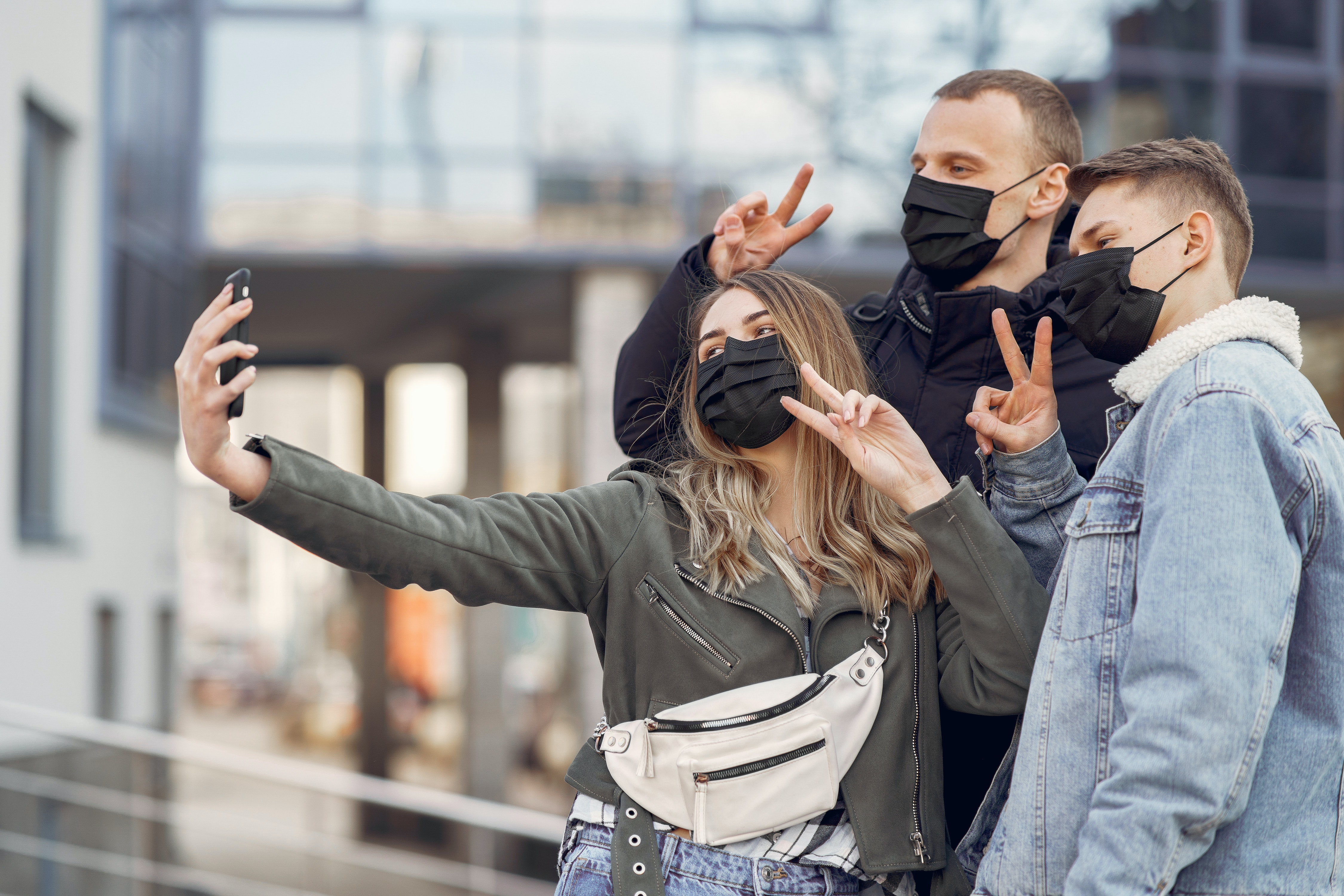 Friends taking a selfie on a smartphone during the pandemic.