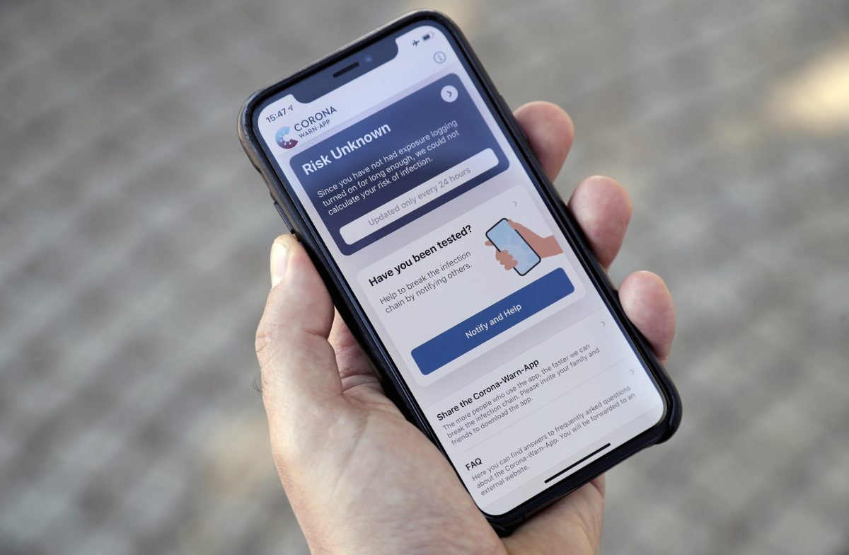 A person holds a smartphone with the official 'Corona Warn-App' (Corona Warning Application) in Berlin, Germany, Monday, June 15, 2020. The app will be introduced on Tuesday, June 16 by the German authorities.