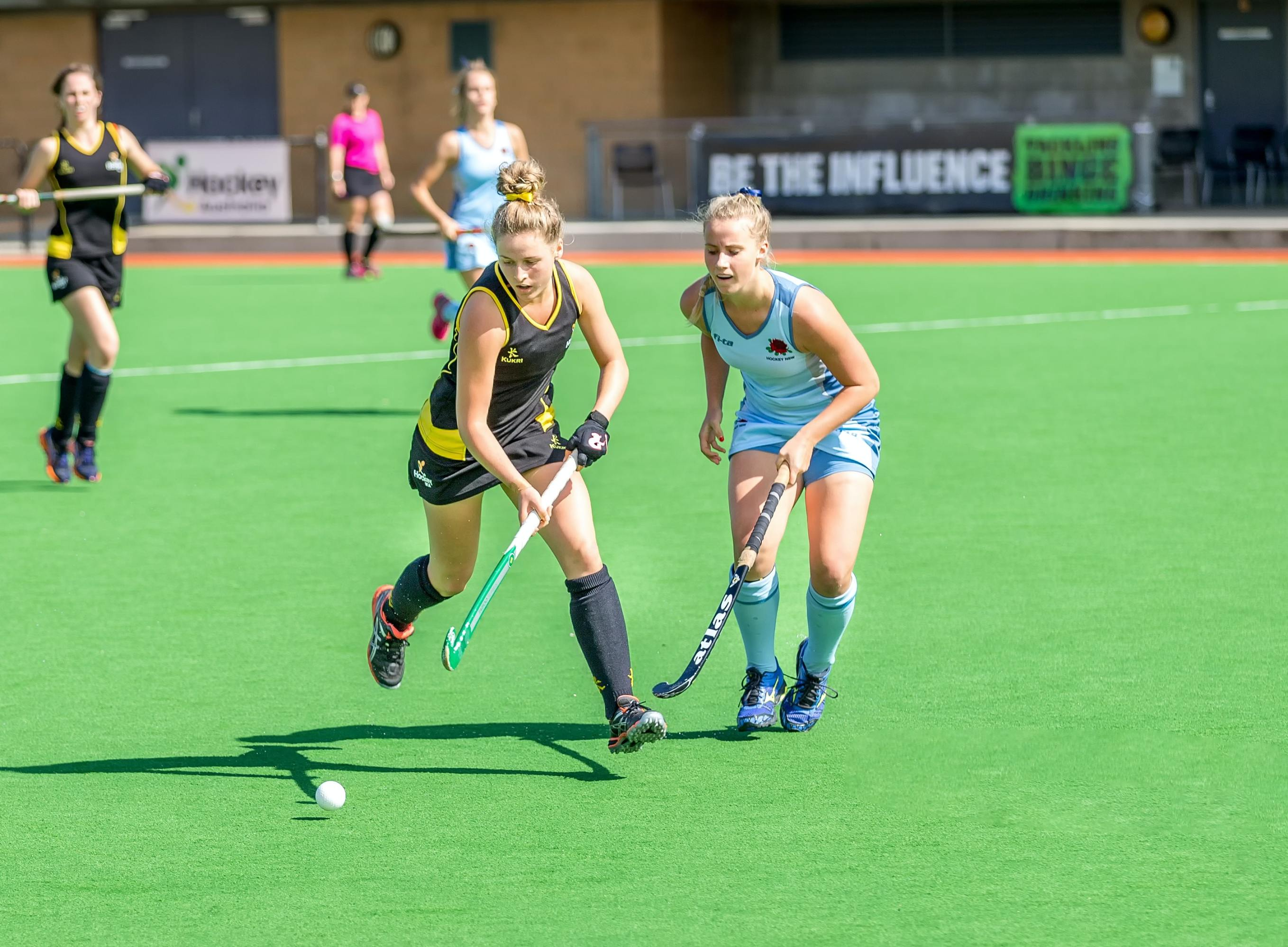 Women playing field hockey