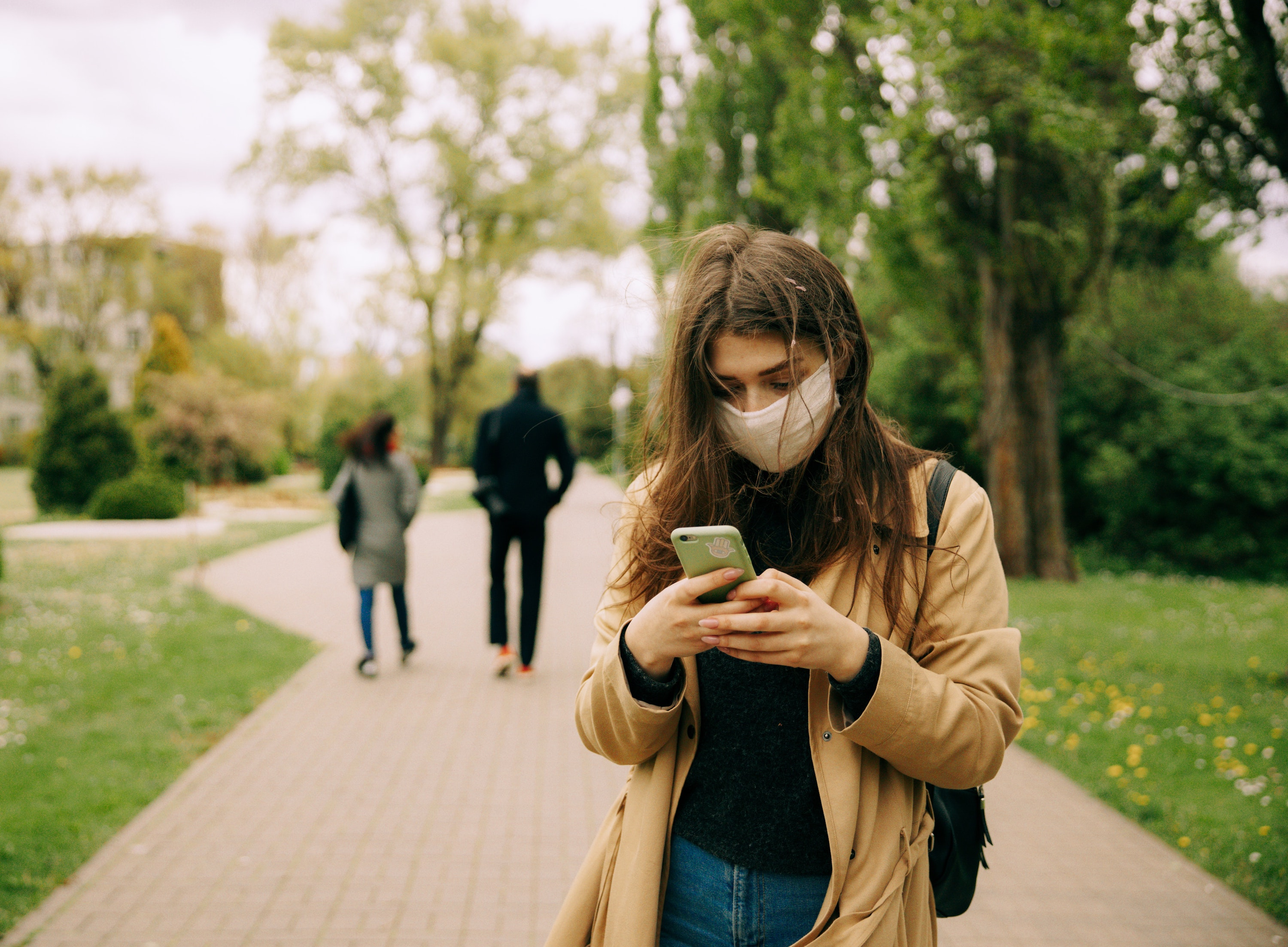 Woman on smartphone wearing face mask, with two people walking away in the background.