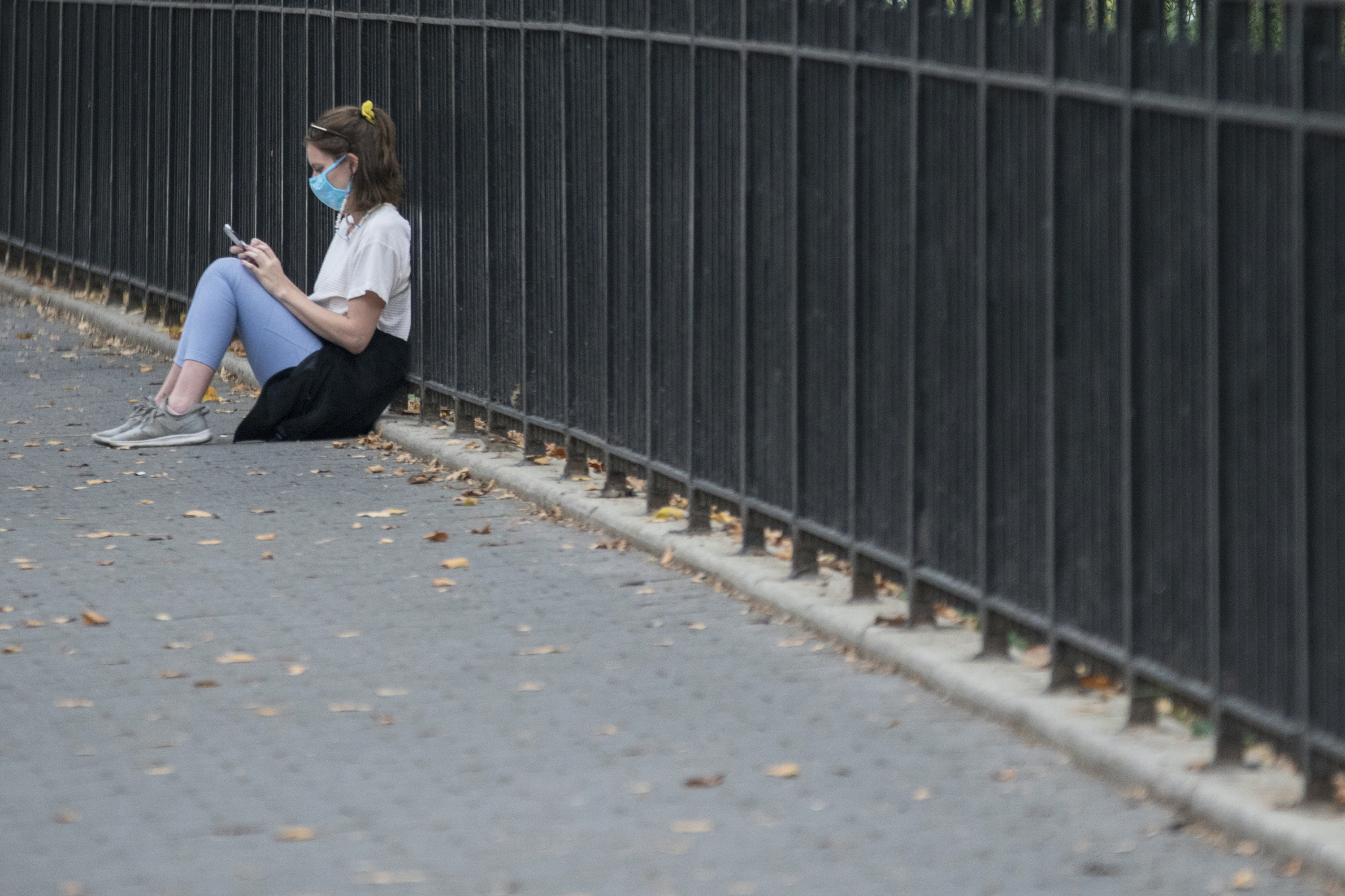 Woman on street looking at phone wearing face mask.