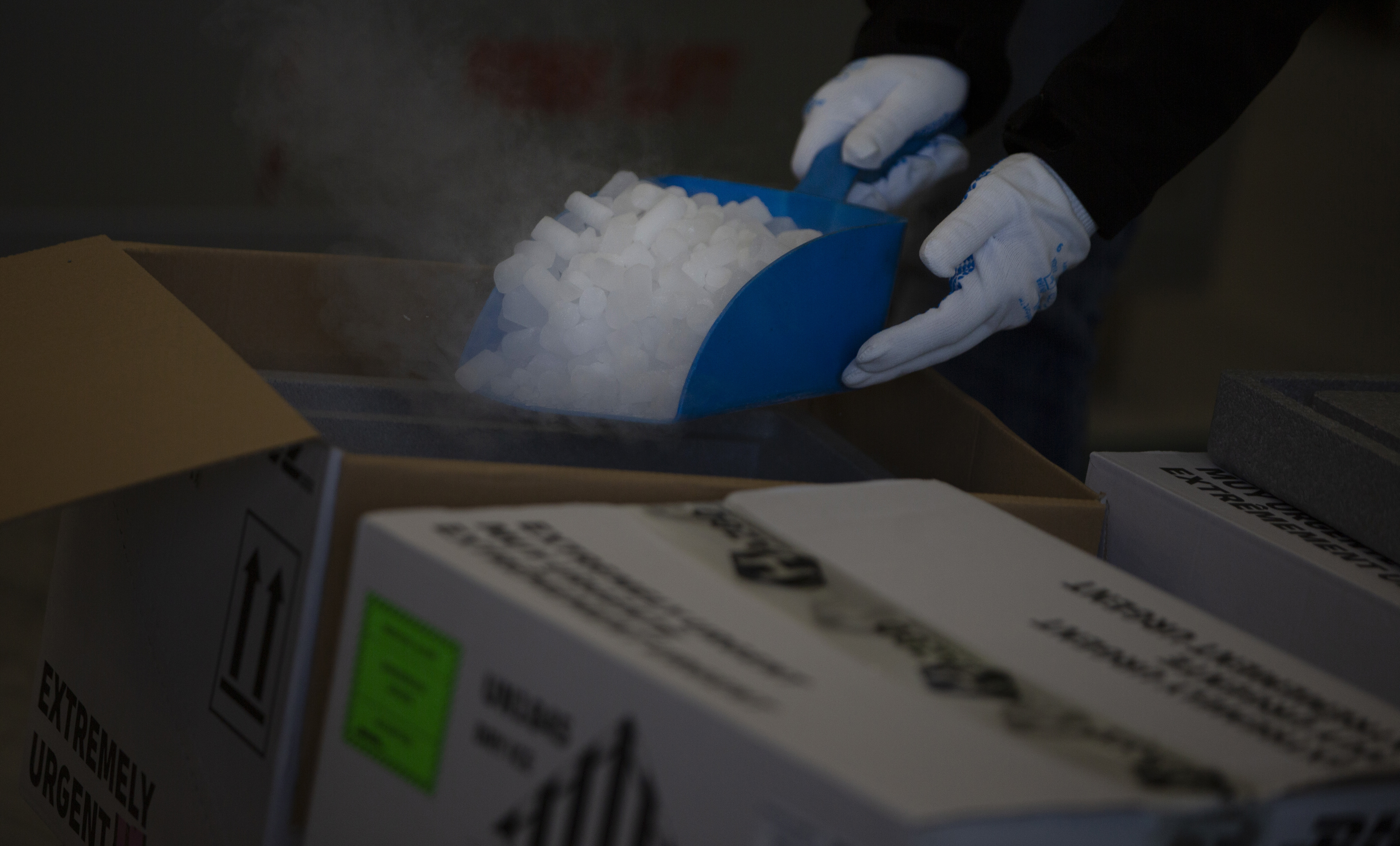 A hazardous goods worker in Belgium shows how dry ice is used to keep vaccines cool.