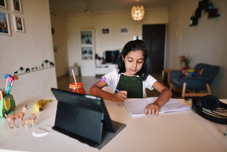 Young girl attending online school