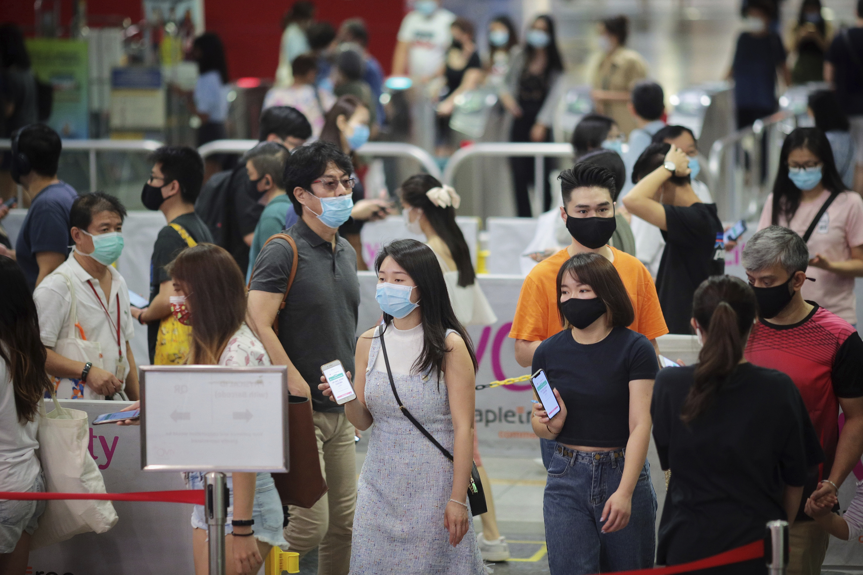 In Singapore, people standing in a long line, holding smartphones and wearing face masks.