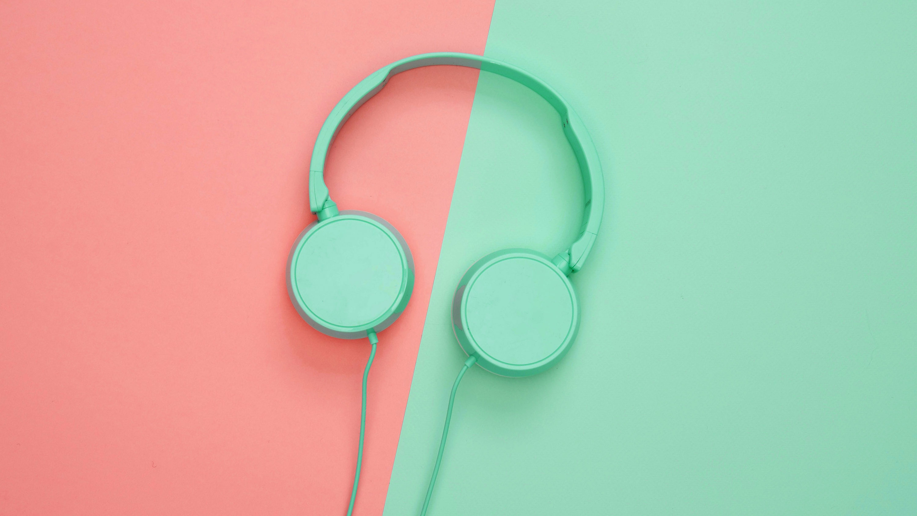 image of mint green headphones laying on split pink and mint background