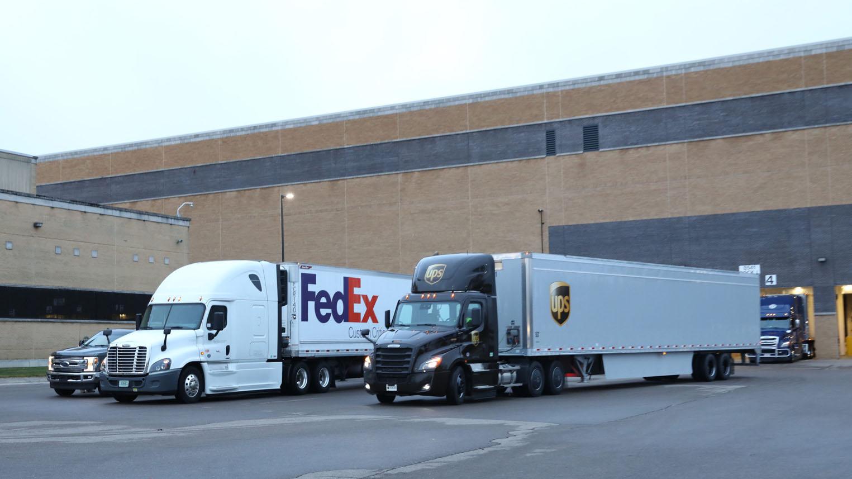FedEx- en UPS-vrachtwagens vertrekken vanaf Pfizer.