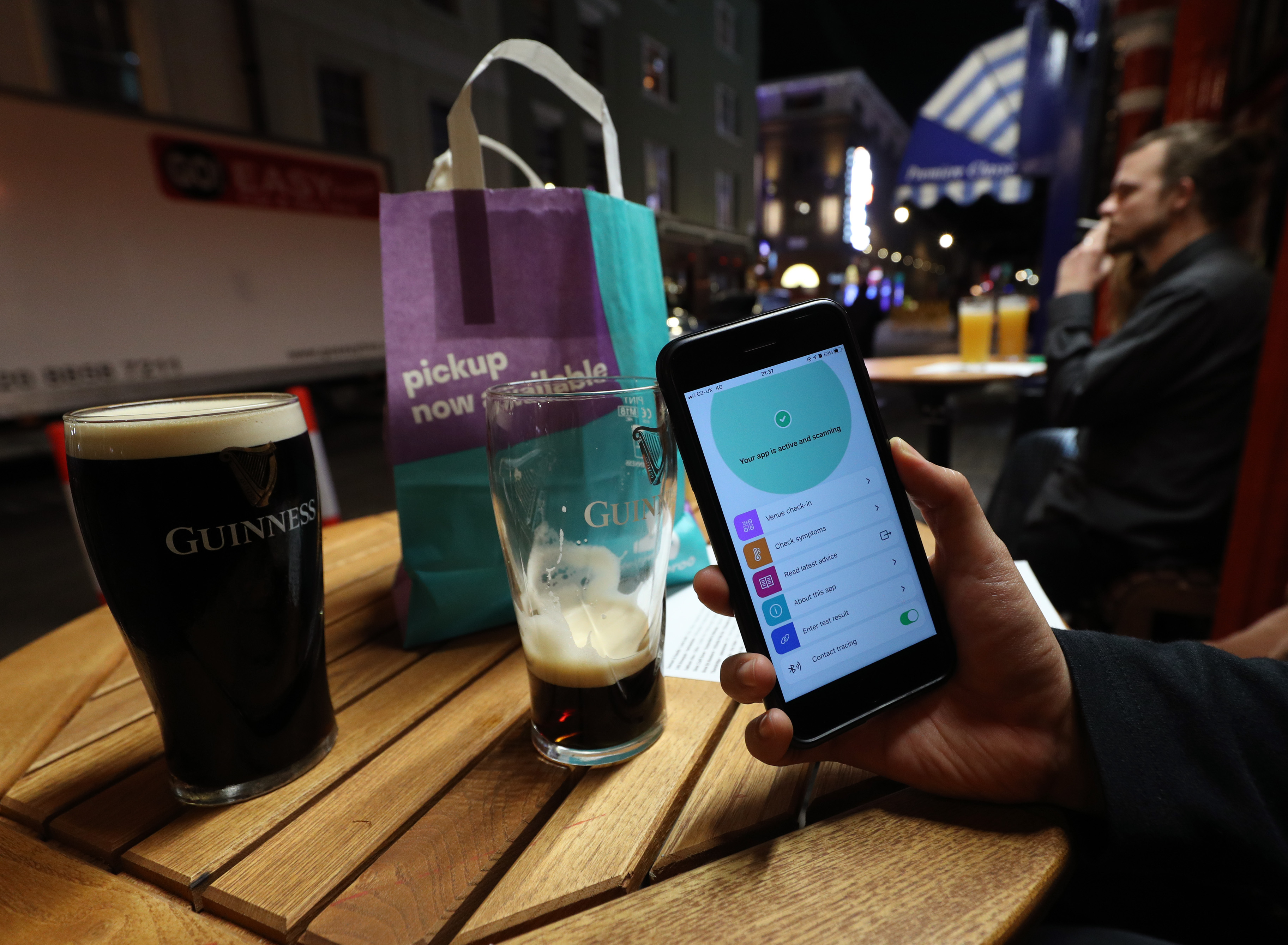 A person uses the NHS coronavirus contact tracing app outside The Coach and Horses pub in Soho, central London, after a range of new restrictions to combat the rise in coronavirus cases came into place in England.