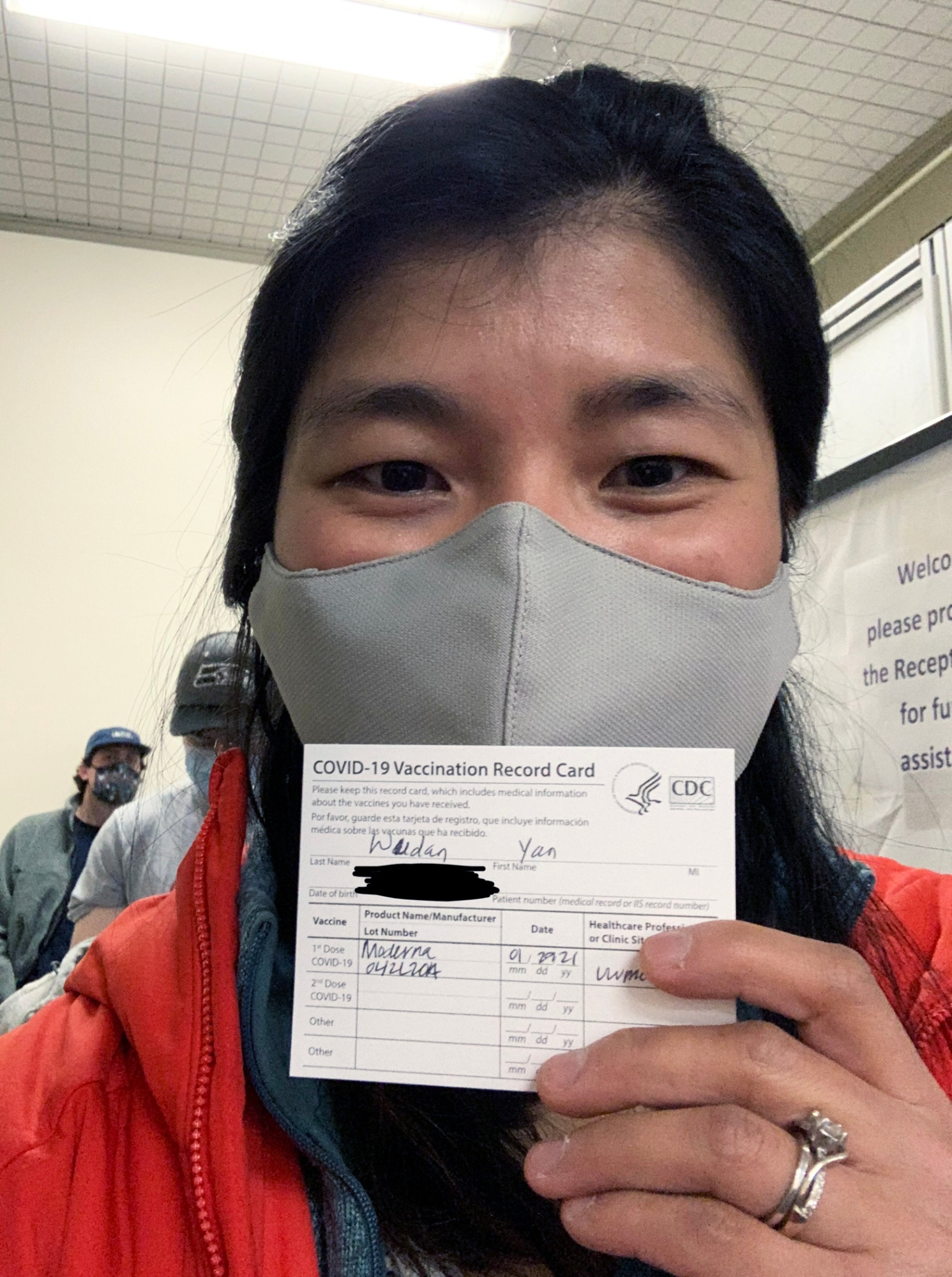 Photograph of Wudan Yan holding her vaccination record card