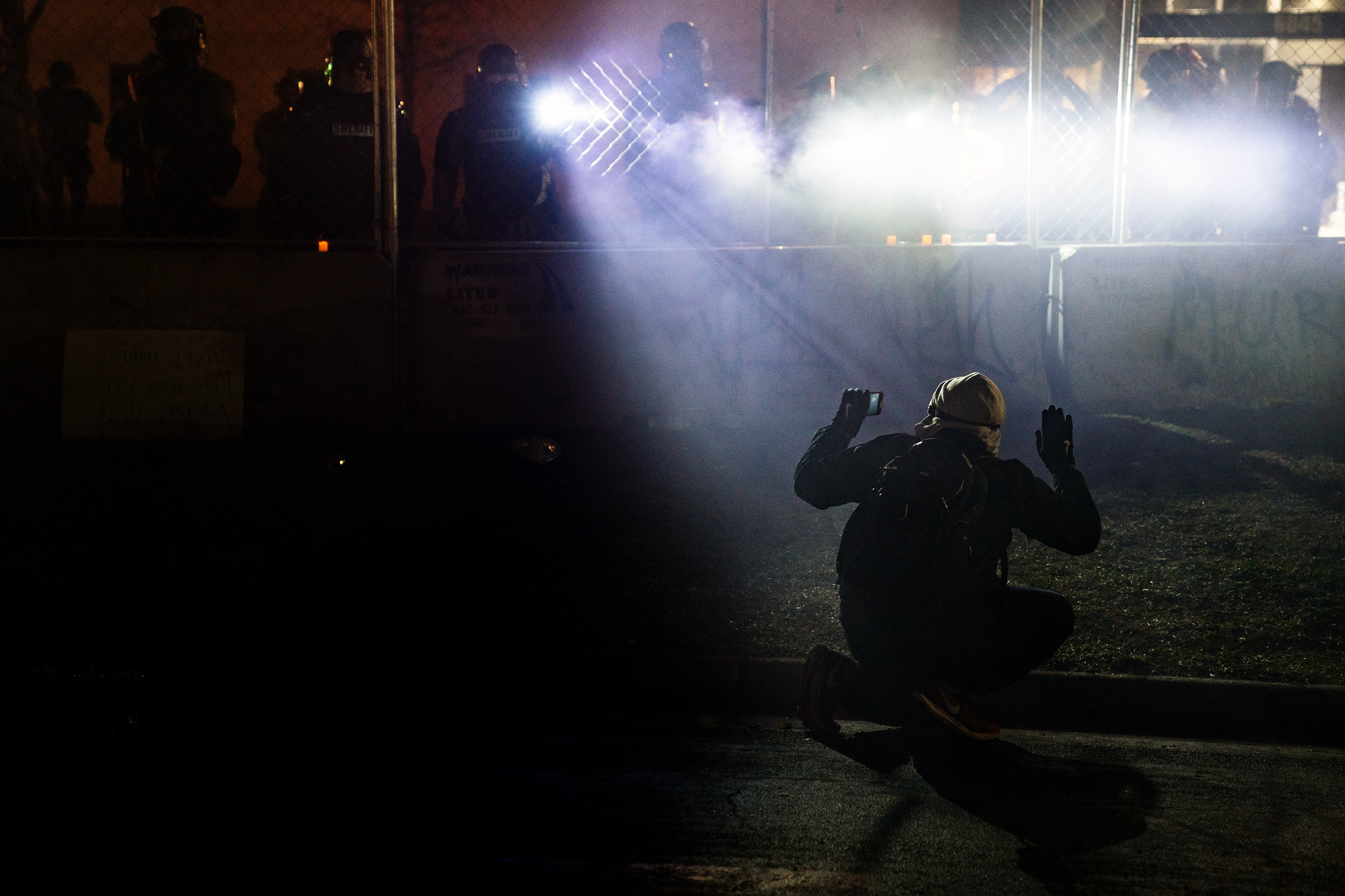 police shine bright lights on protestor filming