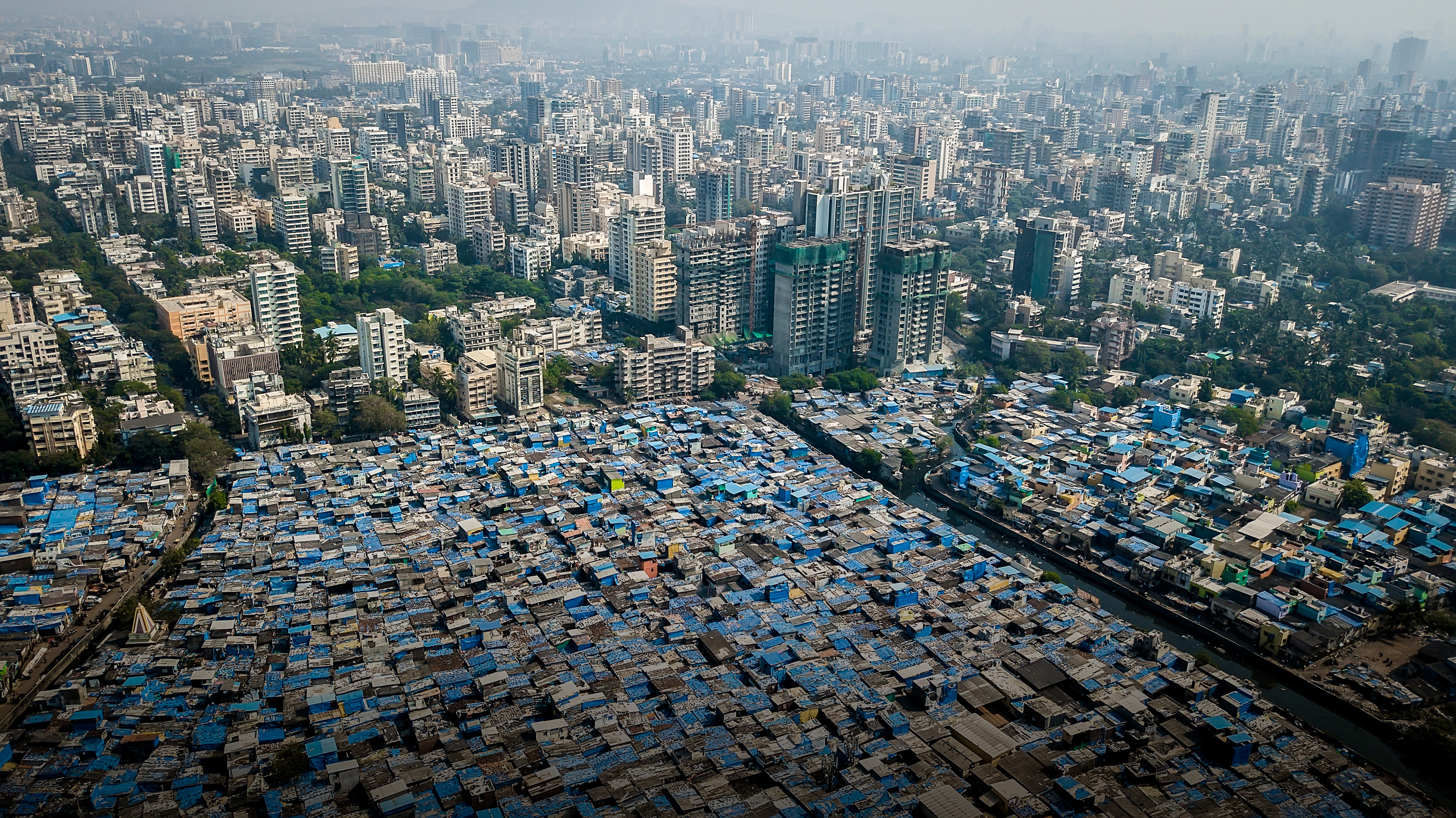 Parts of Mumbai are among the mostly densely populated areas on the planet. In some places, more than a million people live in less than one square mile. Tightly packed buildings, largely made of gray concrete covered with blue tarps, protect against the monsoon rains.