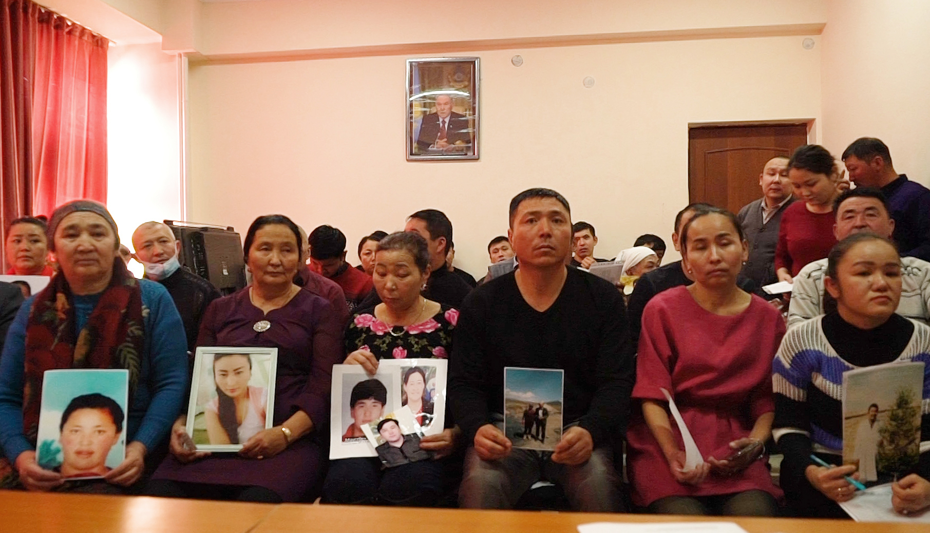 Relatives of people missing in Xinjiang hold up photos at an office of an advocacy organization in Kazakhstan in 2018.