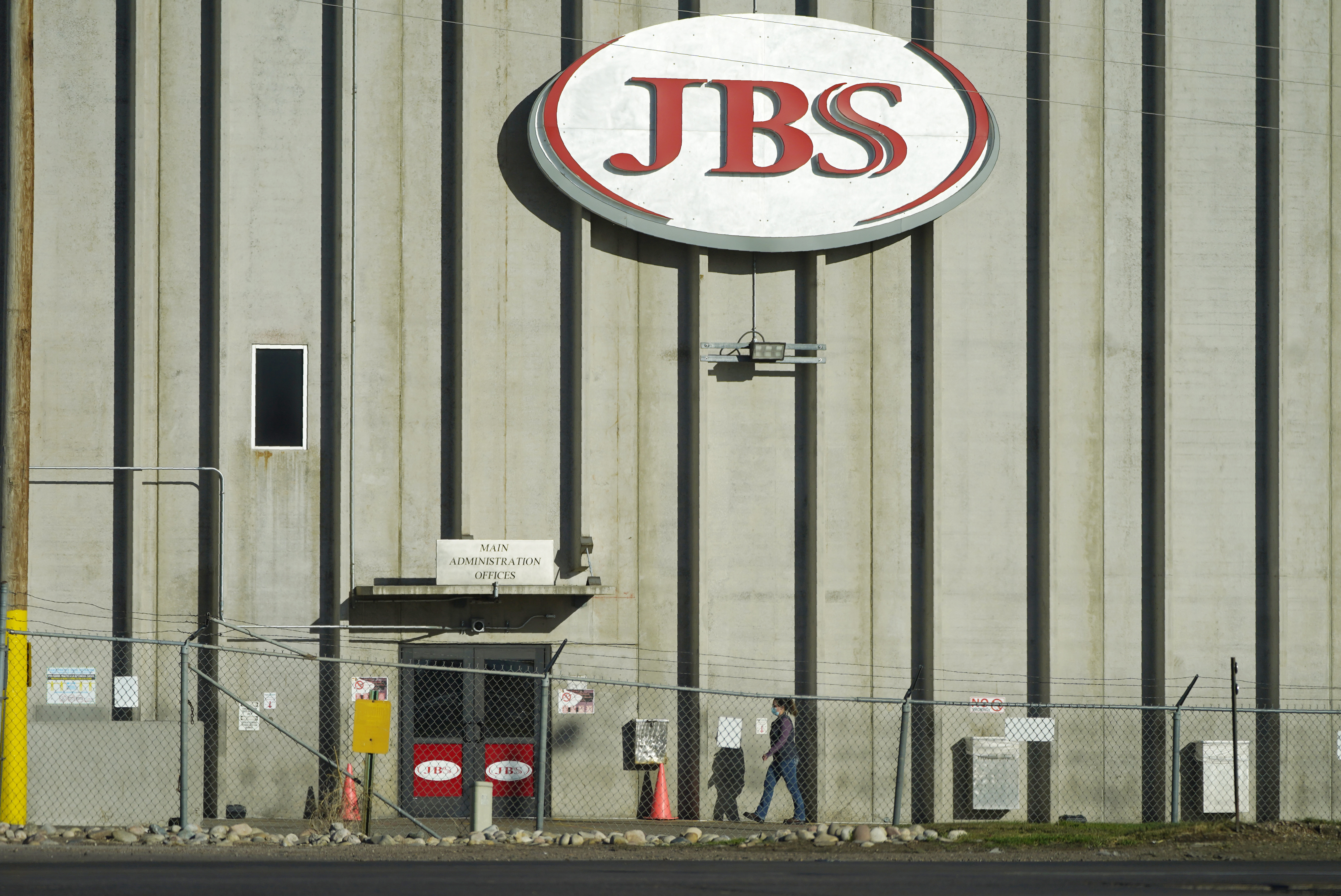 In this Oct. 12, 2020 file photo, a worker heads into the JBS meatpacking plant in Greeley, Colo. A weekend ransomware attack on the world's largest meat company is disrupting production around the world just weeks after a similar incident shut down a U.S. oil pipeline.