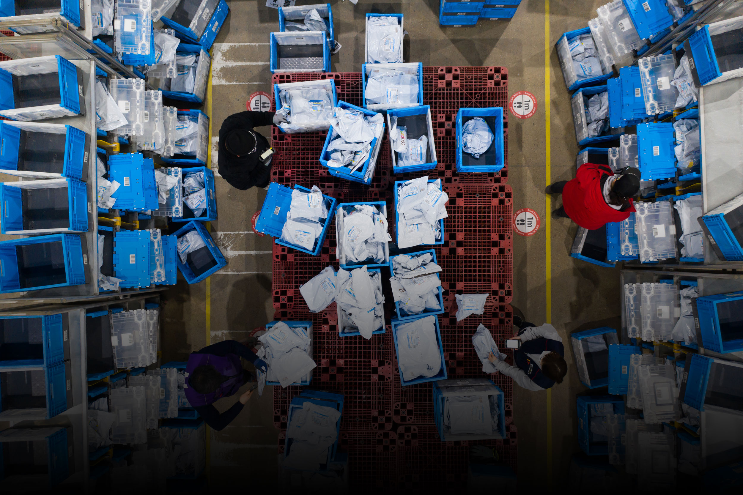 overhead photograph showing a logistics center with employees surrounded by boxes