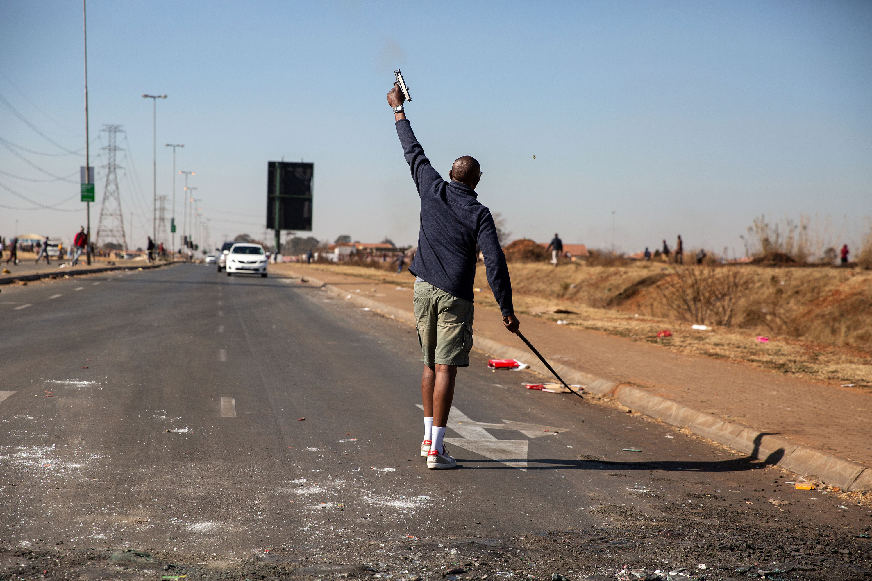 a person shoots a weapon into the air on a road in south africa.